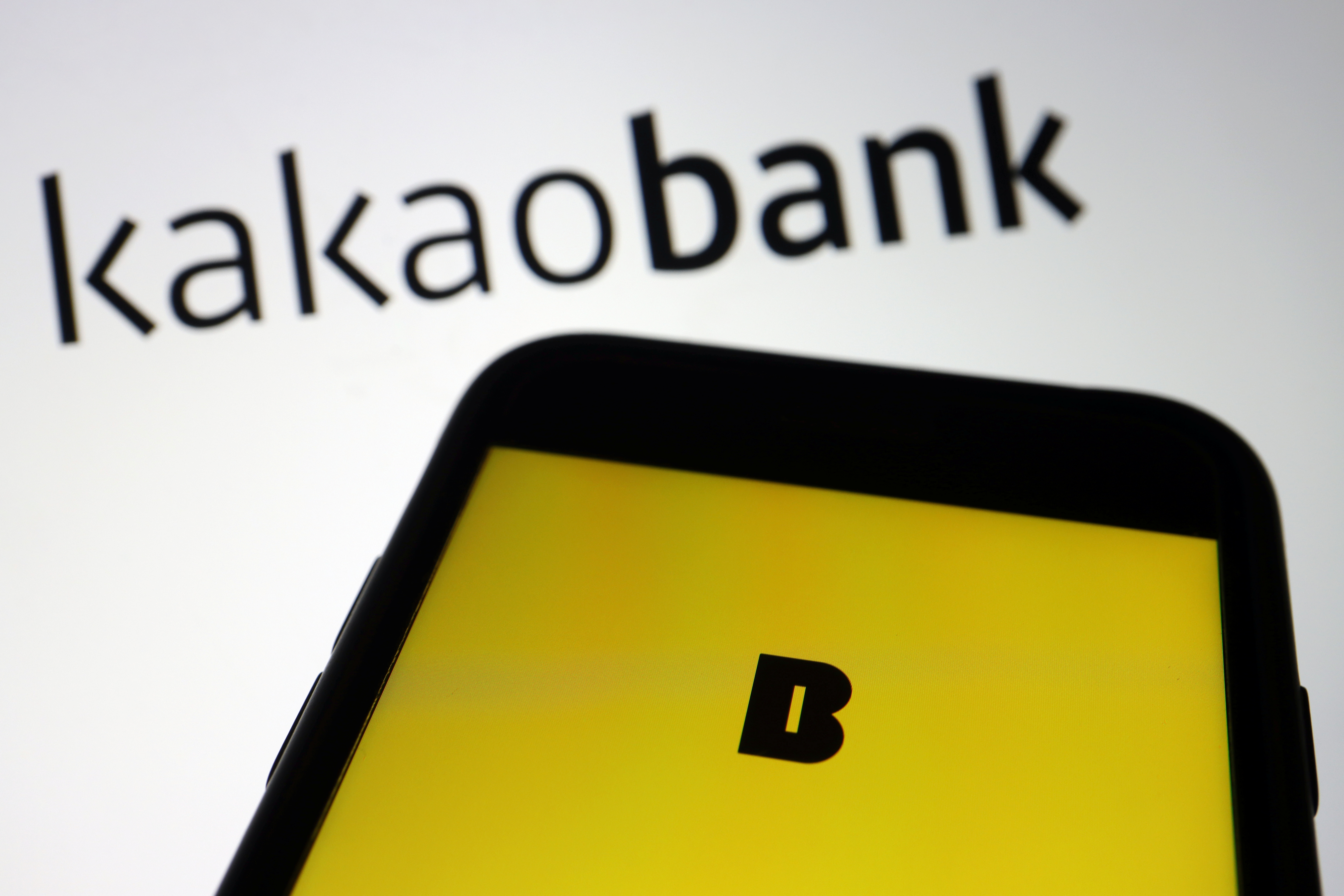 The Kakao Bank app is seen on a mobile phone screen displayed in front of the South Korean digital lender's logo in this illustration picture taken August 6, 2021. REUTERS/Florence Lo/Illustration