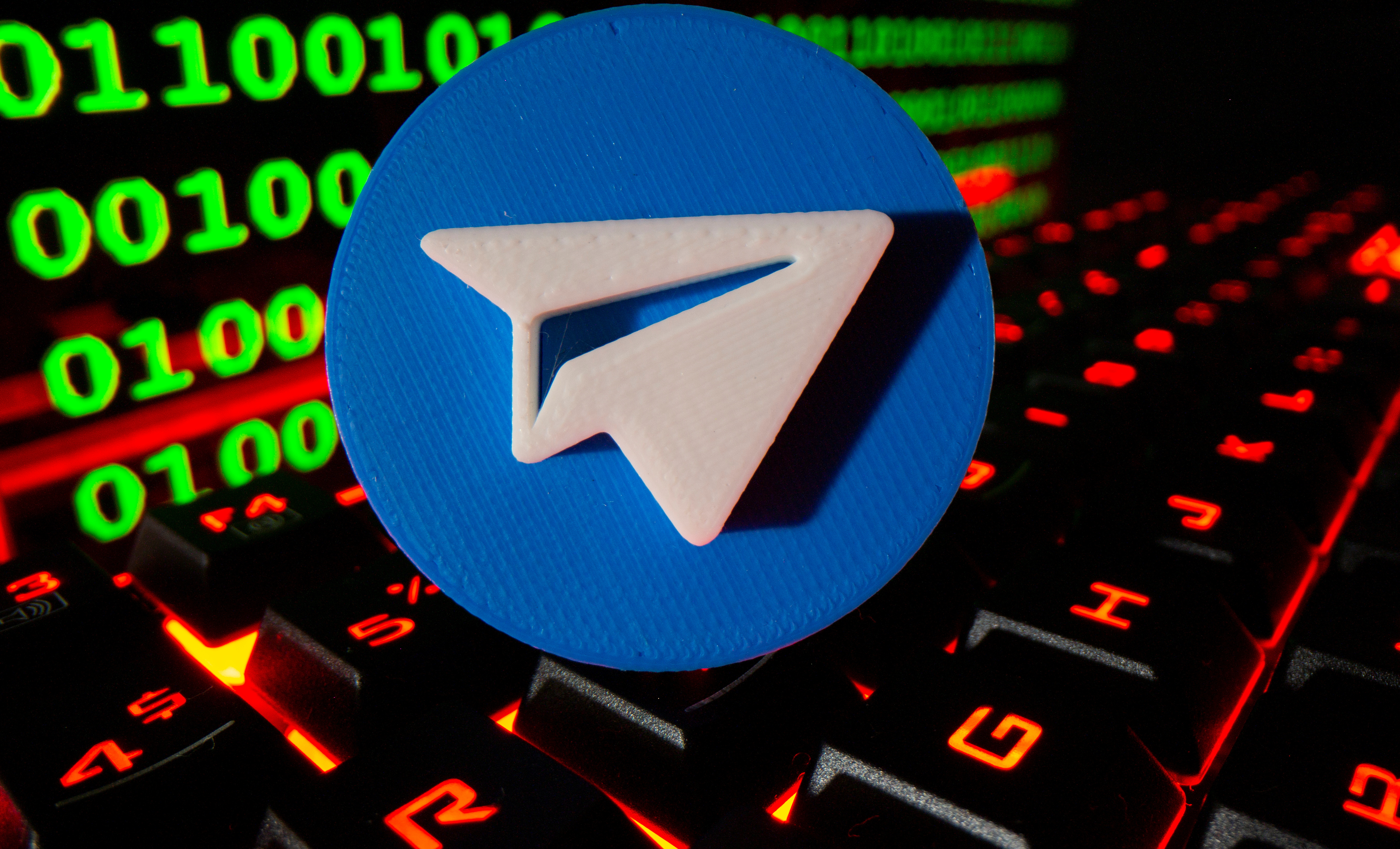 A 3D printed Telegram logo is pictured on a keyboard in front of binary code in this illustration taken September 24, 2021. REUTERS/Dado Ruvic/Illustration