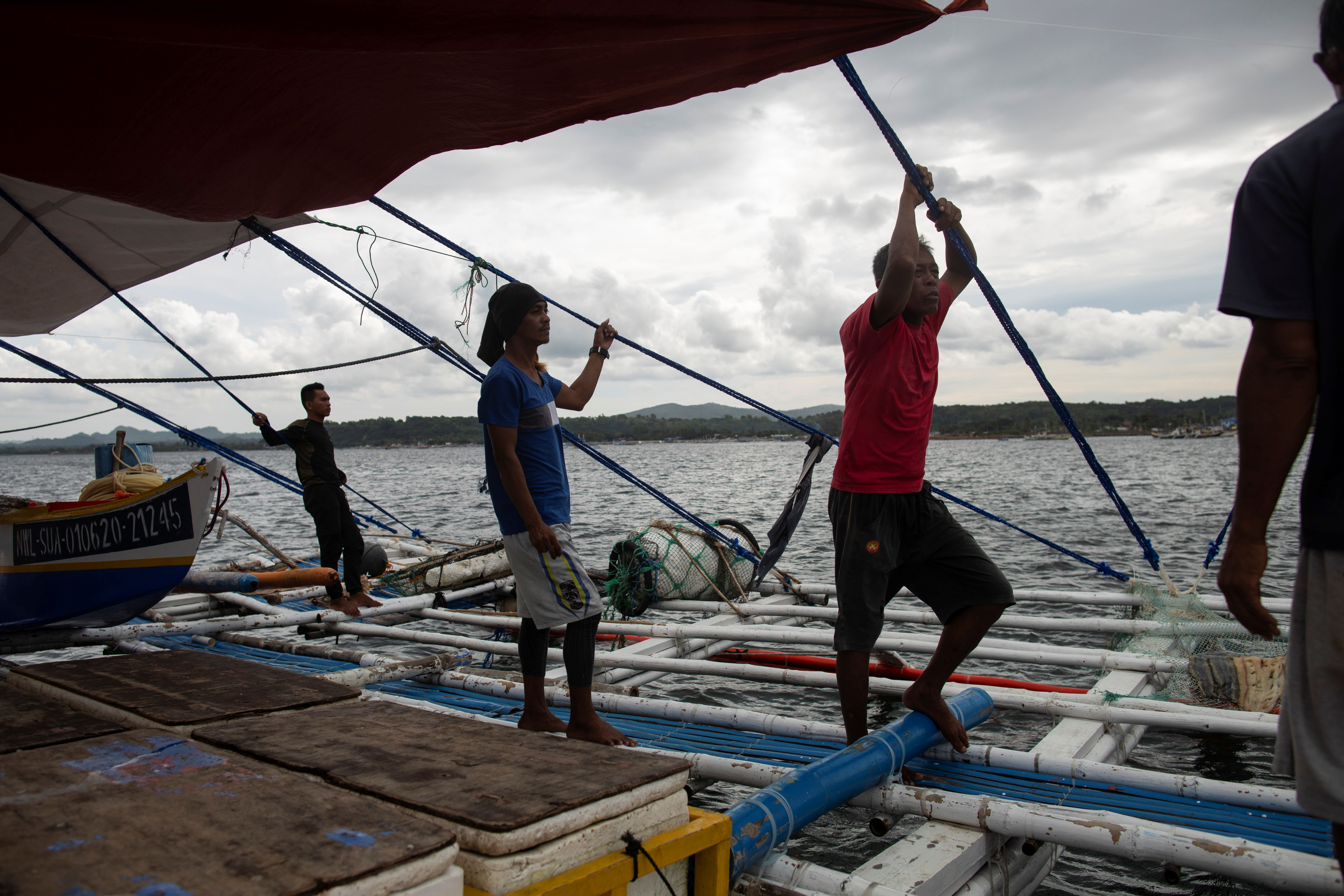 Filipino fishermen rest after arriving from a week-long trip to the disputed Scarborough Shoal, in Infanta, Pangasinan province, Philippines, July 6, 2021. Picture taken July 6, 2021. REUTERS/Eloisa Lopez
