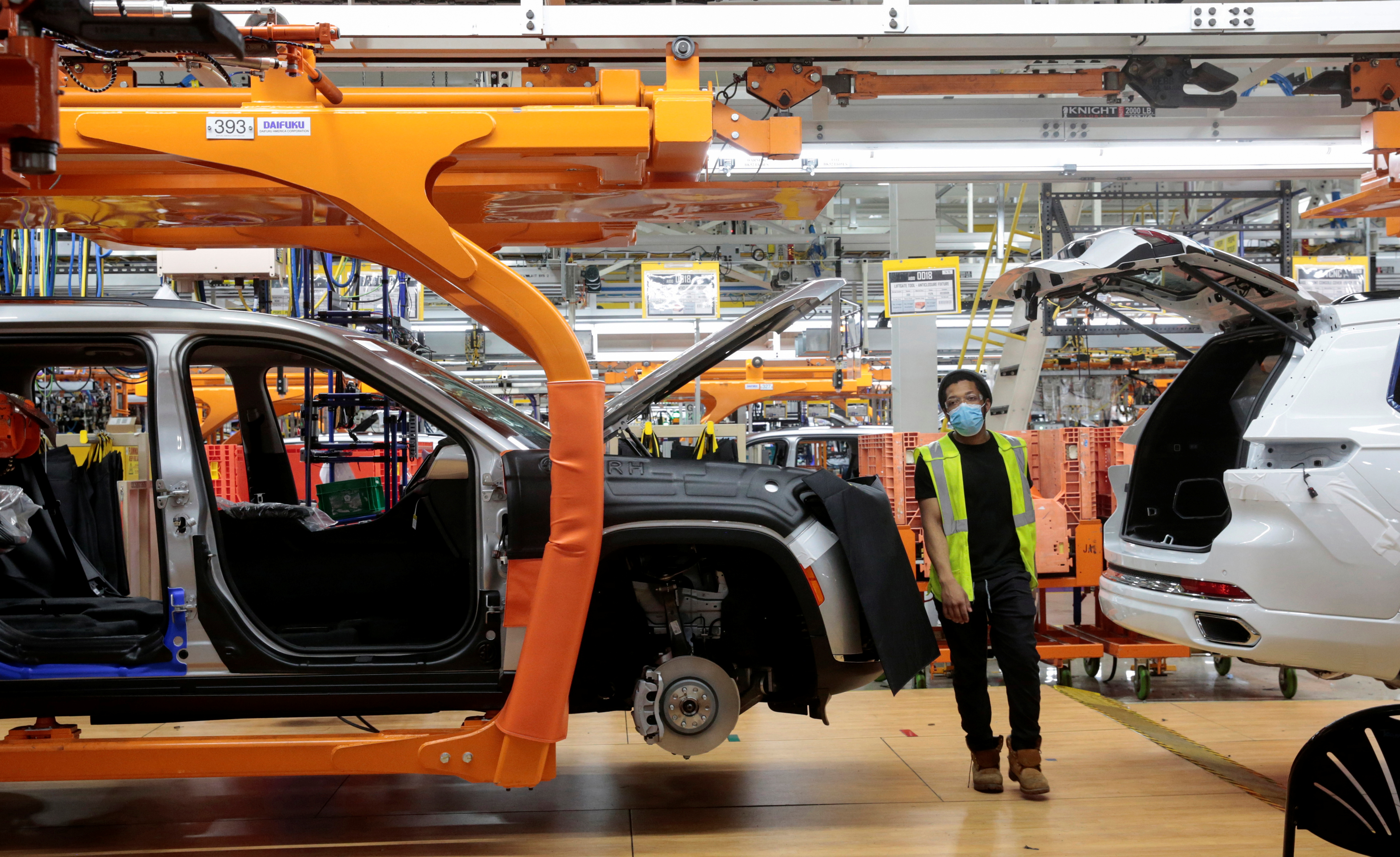 A Stellantis assembly worker walks between two 2021 Jeep Grand Cherokee L vehicles on the assembly line at the Detroit Assembly Complex - Mack Plant in Detroit, Michigan, U.S., June 10, 2021. Picture taken June 10, 2021. REUTERS/Rebecca Cook