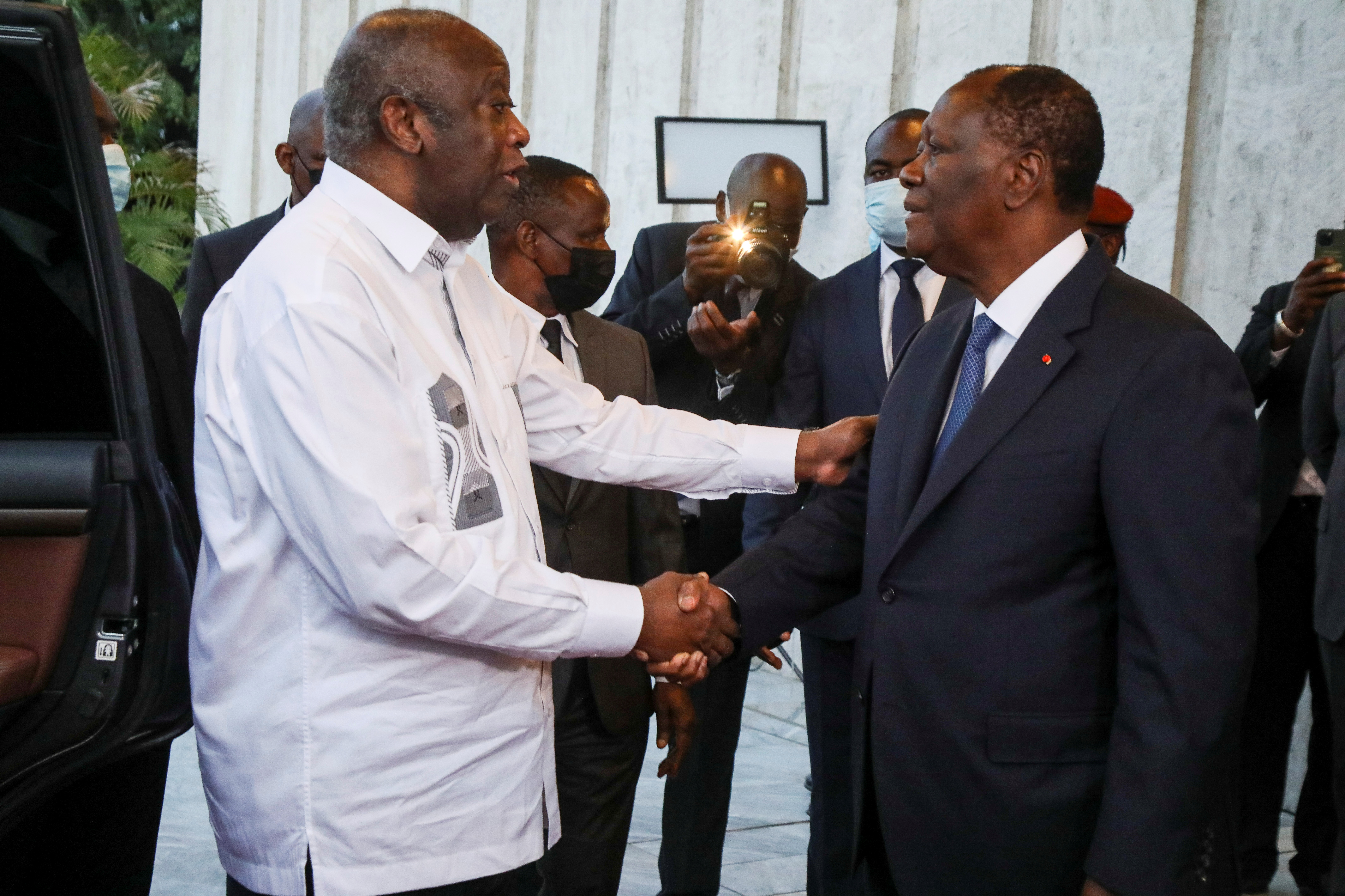 Ivory Coast's President Alassane Ouattara shakes hands with former Ivory Coast President Laurent Gbagbo during a meeting at the presidential palace in Abidjan, Ivory Coast July 27, 2021. REUTERS/Luc Gnago