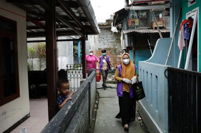 Health care workers walk through a neighborhood of Sindanglaya village during a door-to-door vaccination for coronavirus disease (COVID-19) in Cianjur regency, West Java province, Indonesia, June 15, 2021. REUTERS/Willy Kurniawan