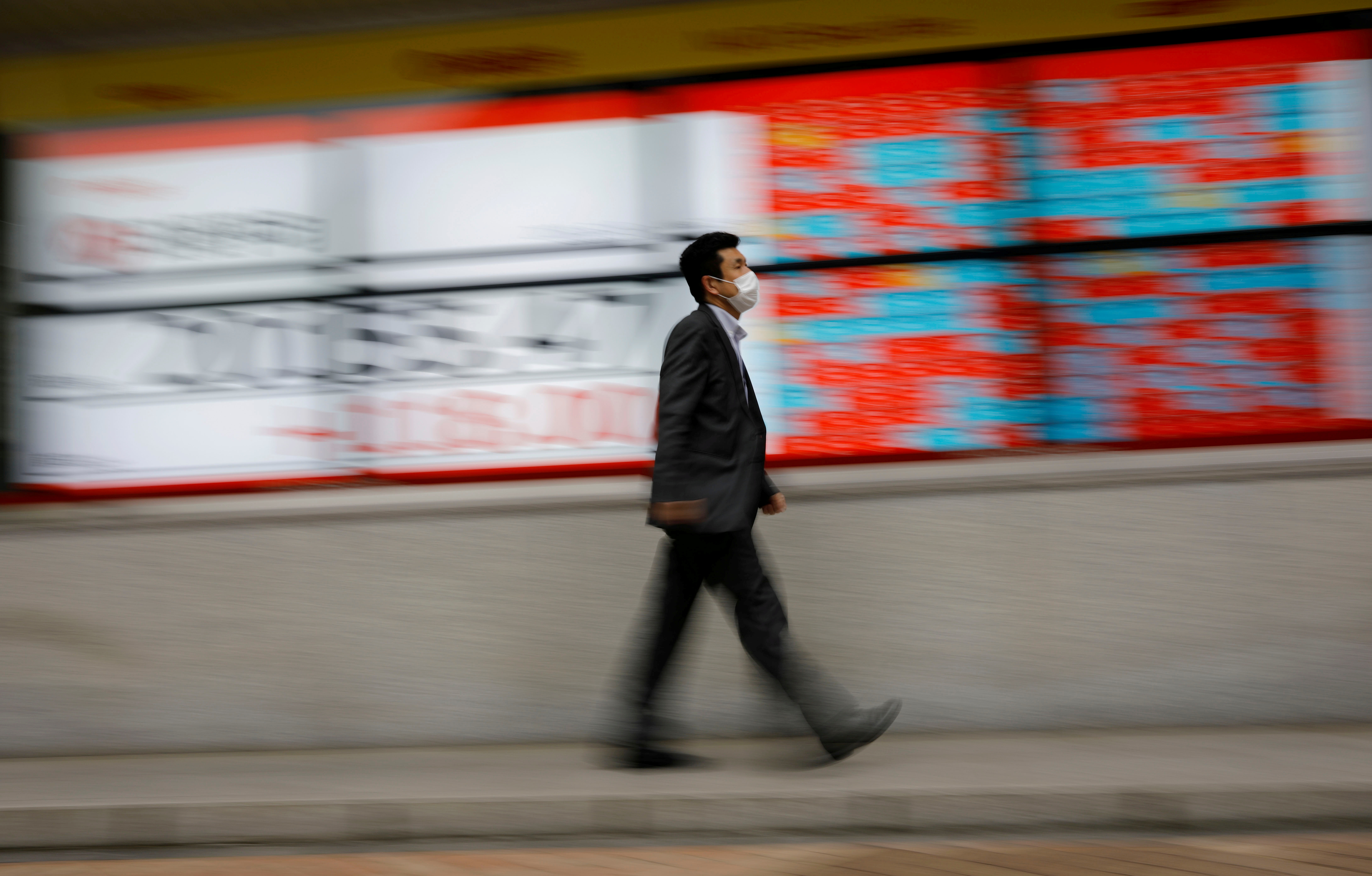 A man wearing a protective face mask, following the coronavirus disease (COVID-19) outbreak, walks in front of a stock quotation board outside a brokerage in Tokyo, Japan, May 18, 2020. REUTERS/Kim Kyung-Hoon/File Photo