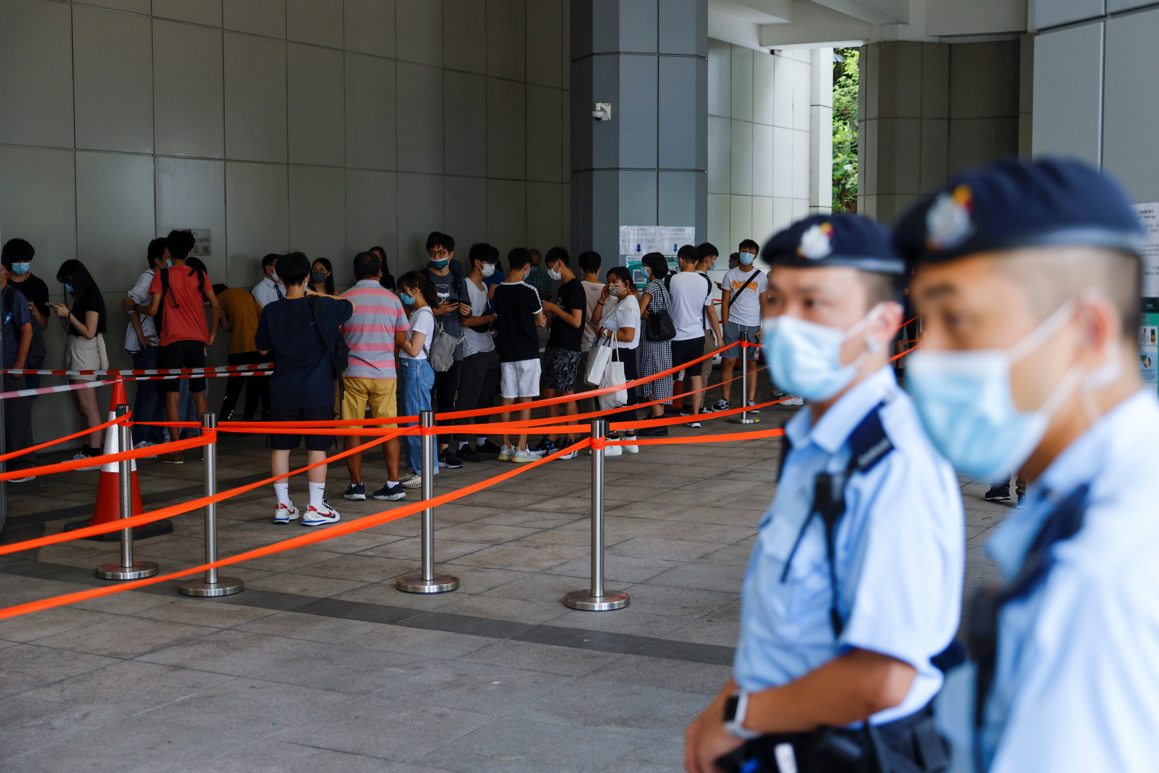 Supporters of Tong Ying-kit, the first person charged under a new national security law, queue up for attending the hearing at the High Court in Hong Kong, China. July 30, 2021. REUTERS/Tyrone Siu