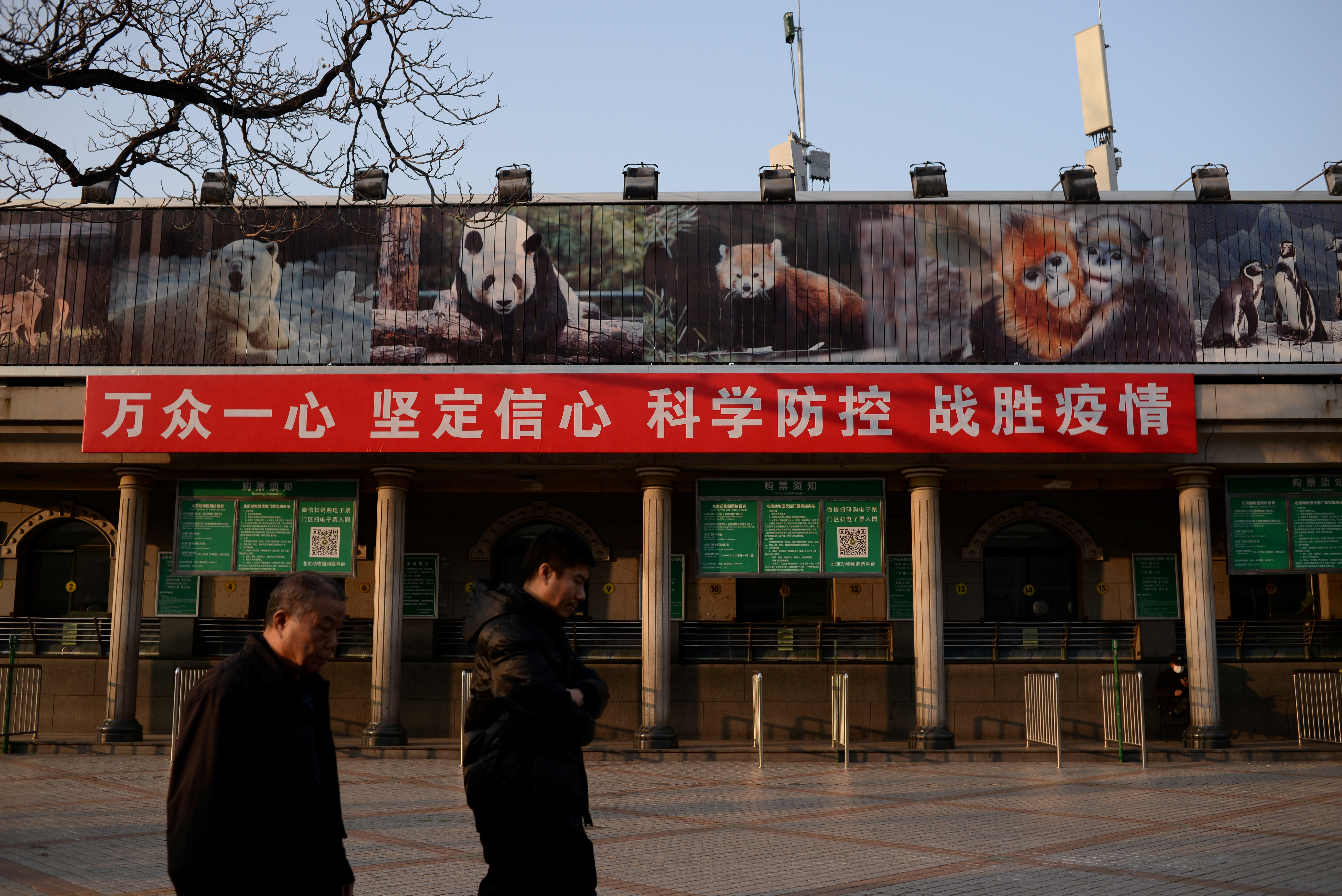 Men walk past a banner hung on the ticket office of the Beijing Zoo that is closed following an outbreak of the novel coronavirus in the country, in Beijing, China February 10, 2020. The Chinese characters on the banner read,