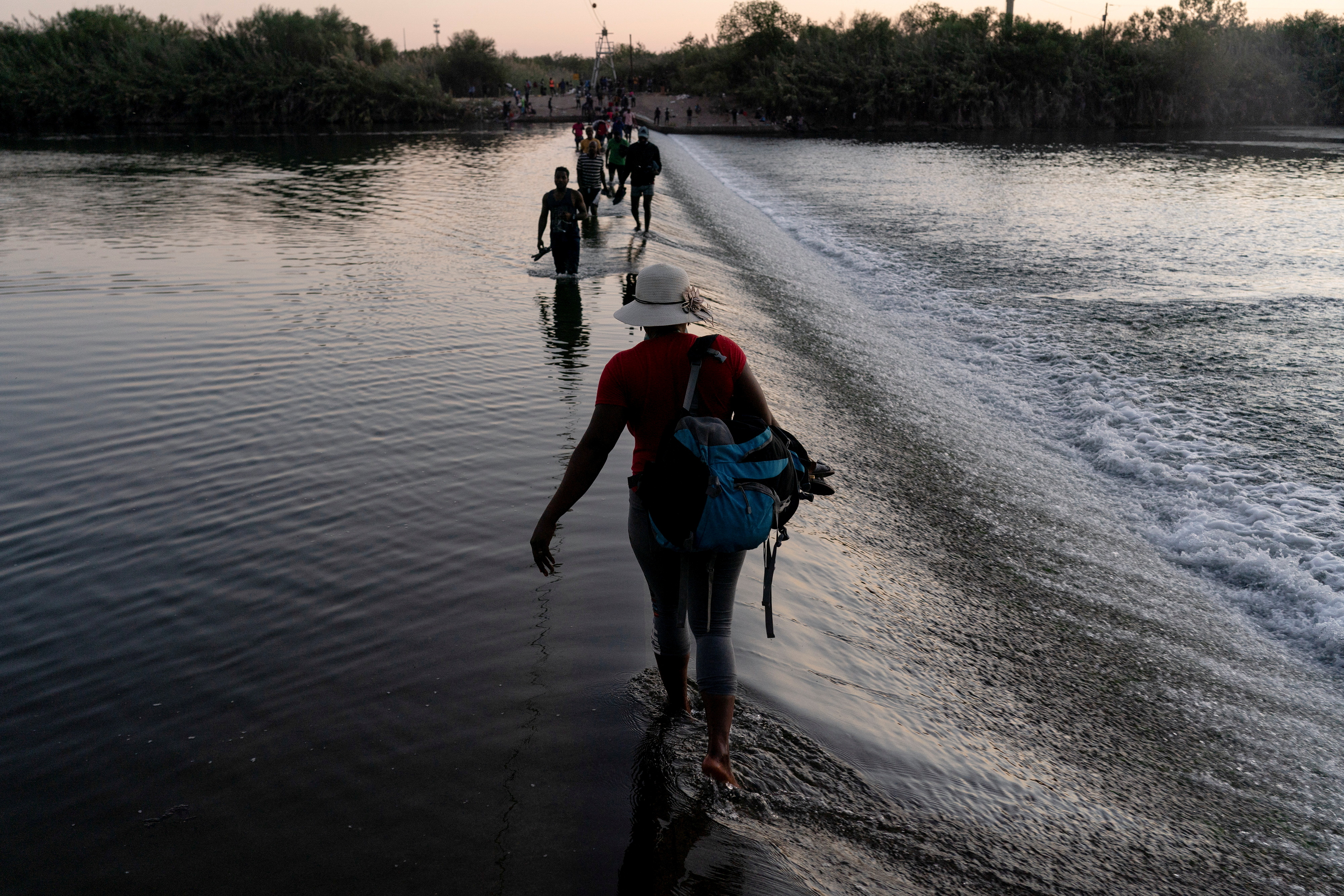 Migrants seeking asylum in the U.S. walk in the Rio Grande river near the International Bridge between Mexico and the U.S. as they wait to be processed, in Ciudad Acuna, Mexico, September 17, 2021. Migrants cross back and forth into Mexico to buy food and supplies. REUTERS/Go Nakamura