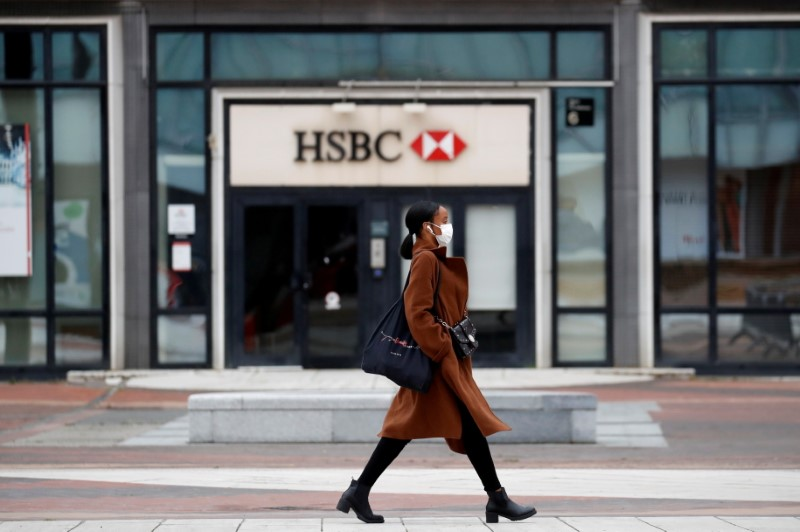 A woman wearing a protective face mask walks past a logo of HSBC bank at the financial and business district of La Defense near Paris as France begun a gradual end to a nationwide lockdown due to the coronavirus disease (COVID-19), May 11, 2020. REUTERS/Gonzalo Fuentes/File Photo