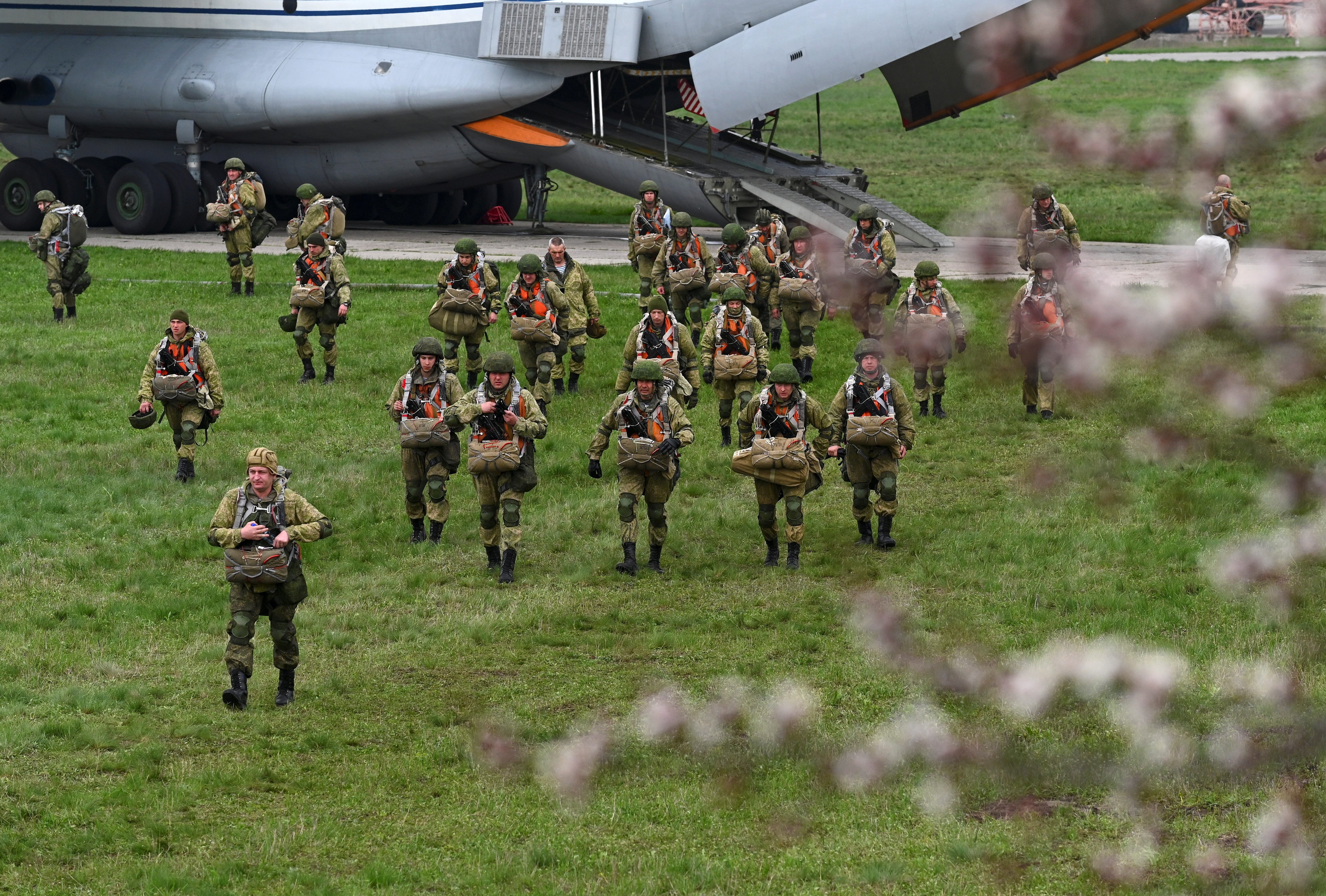 Service members of the Russian airborne forces walk before boarding Ilyushin Il-76 transport planes during drills at a military aerodrome in the Azov Sea port of Taganrog, Russia April 22, 2021. REUTERS/Stringer