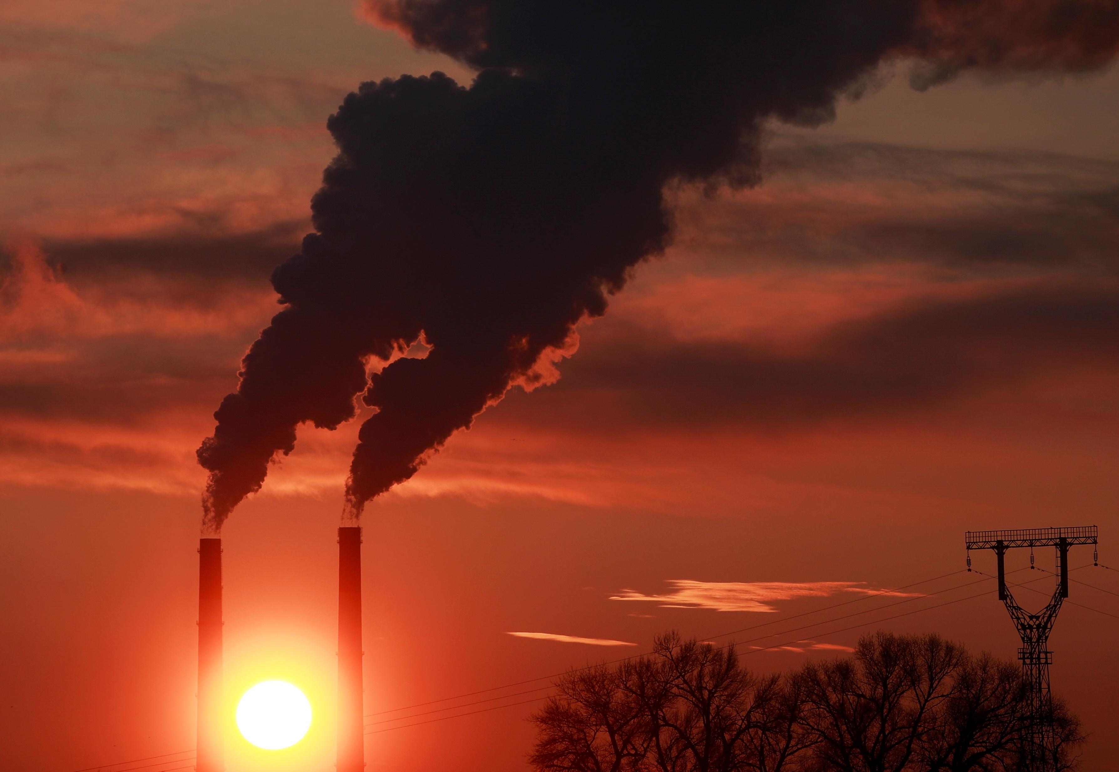 The sun sets behind chimneys of a thermal power plant in Kyiv, Ukraine February 2, 2021.  REUTERS/Valentyn Ogirenko