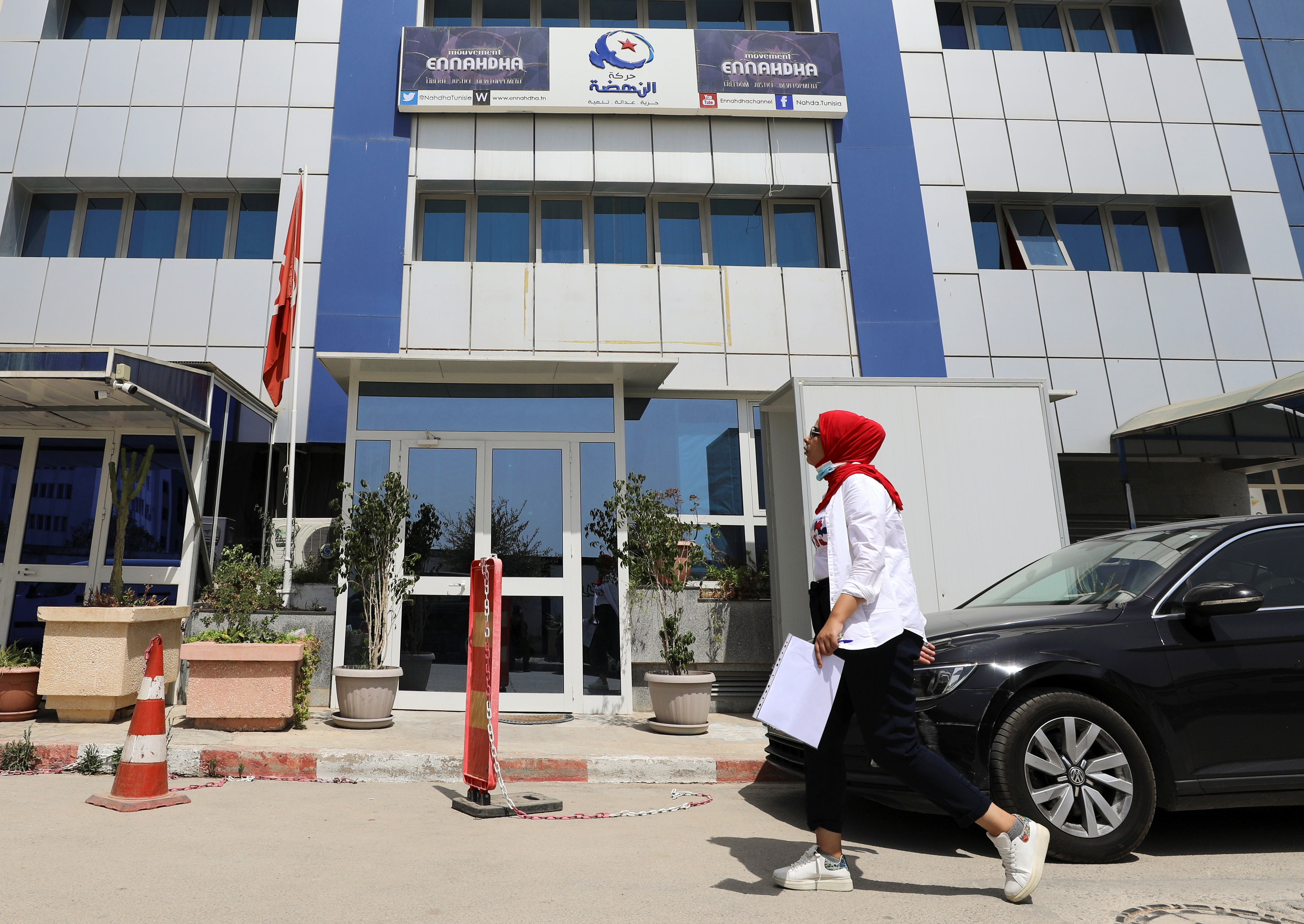 A woman walks past the building of the Islamist Ennahda party headquarters in Tunis, Tunisia, July 29, 2021. REUTERS/