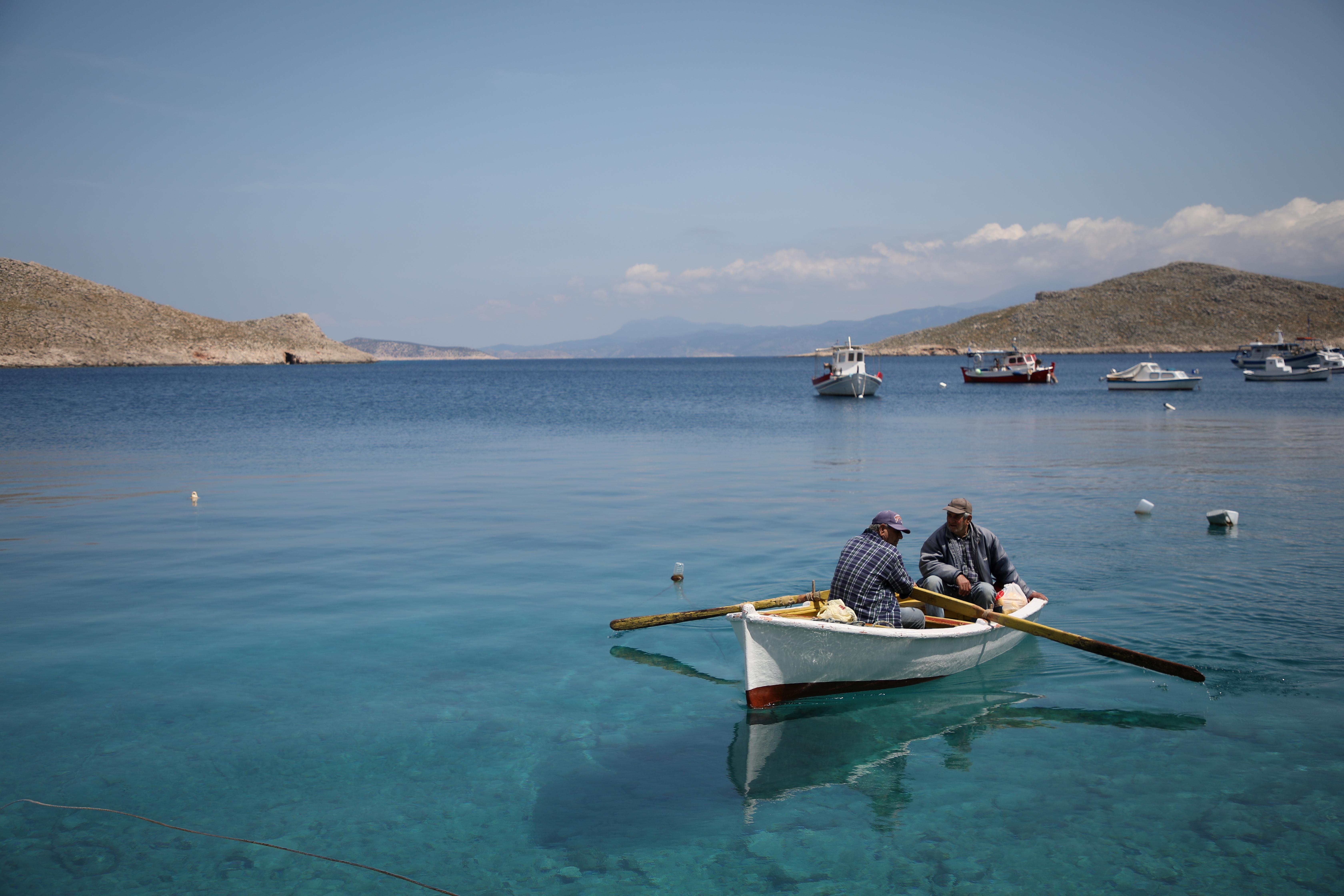 Two fishermen leave the port of Halki on their boat, amid the coronavirus disease (COVID-19) pandemic, on the island of Halki, Greece, April 13, 2021. REUTERS/Louiza Vradi