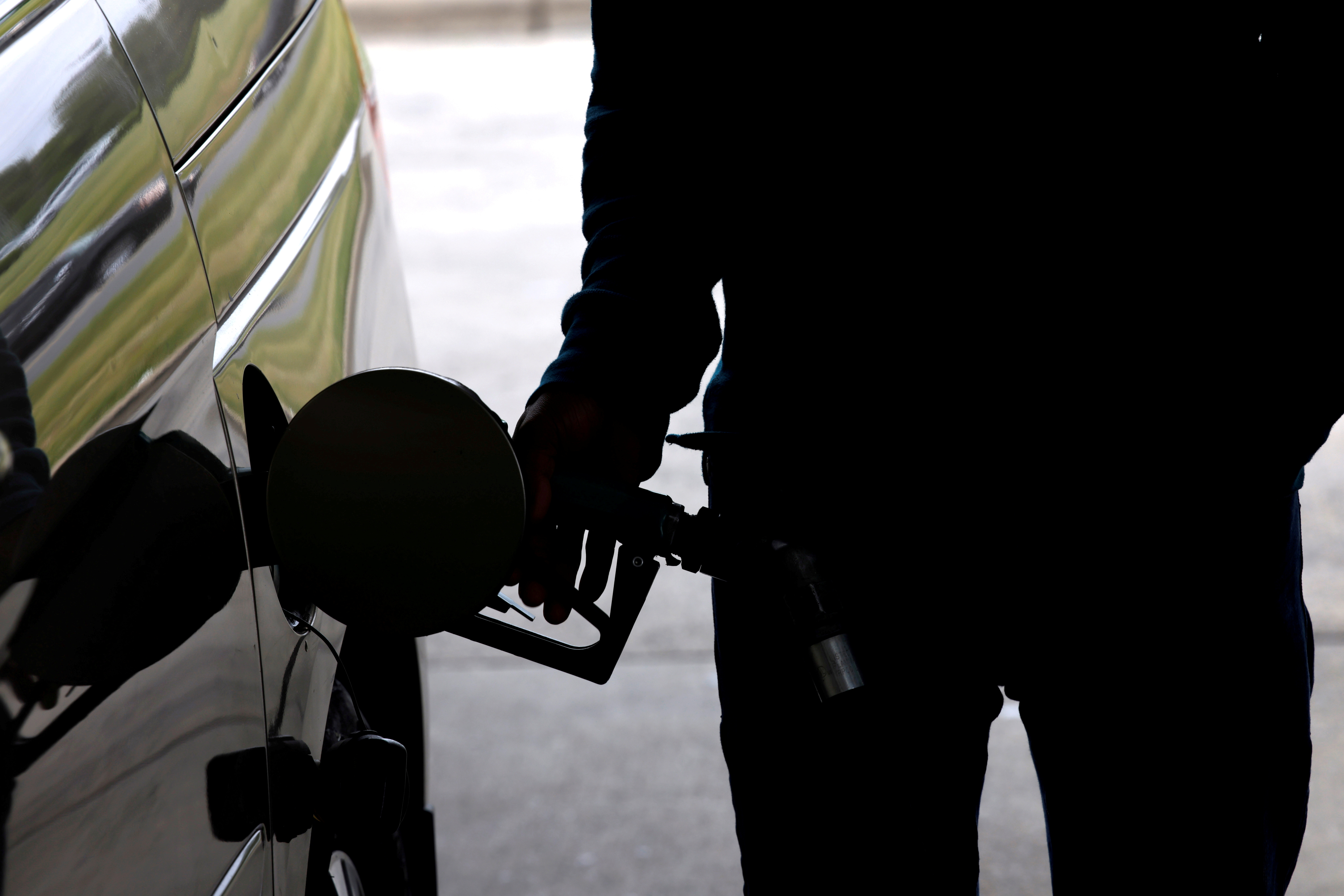 A motorist tops up the fuel in his car's gas tank after a lengthy wait to enter a gasoline station during a surge in the demand for fuel following the cyberattack that crippled the Colonial Pipeline, in Durham, North Carolina, U.S. May 12, 2021.  REUTERS/Jonathan Drake//File Photo