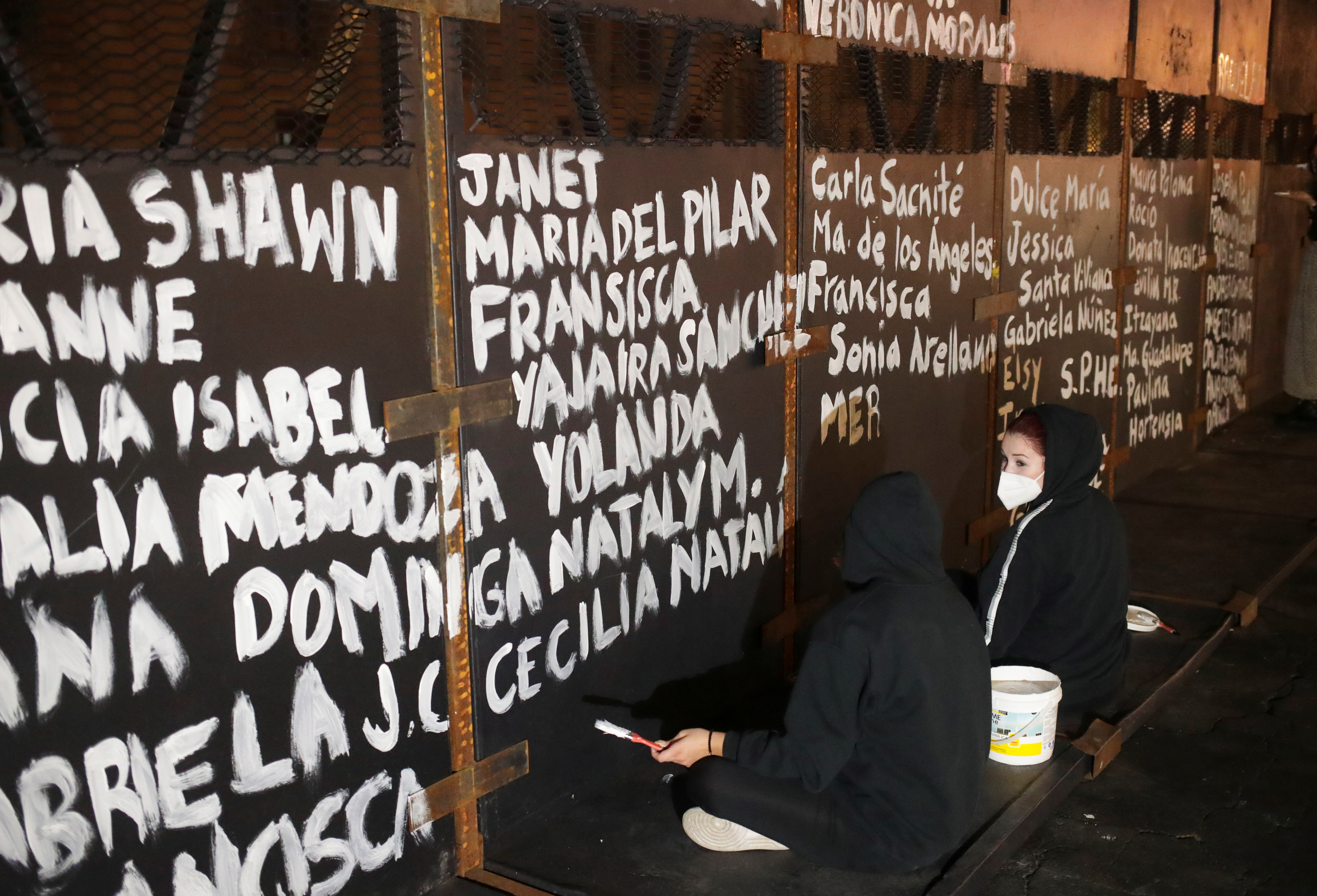 Women paint the names of victims of femicide in Mexico on fences placed outside the National Palace ahead of a Women