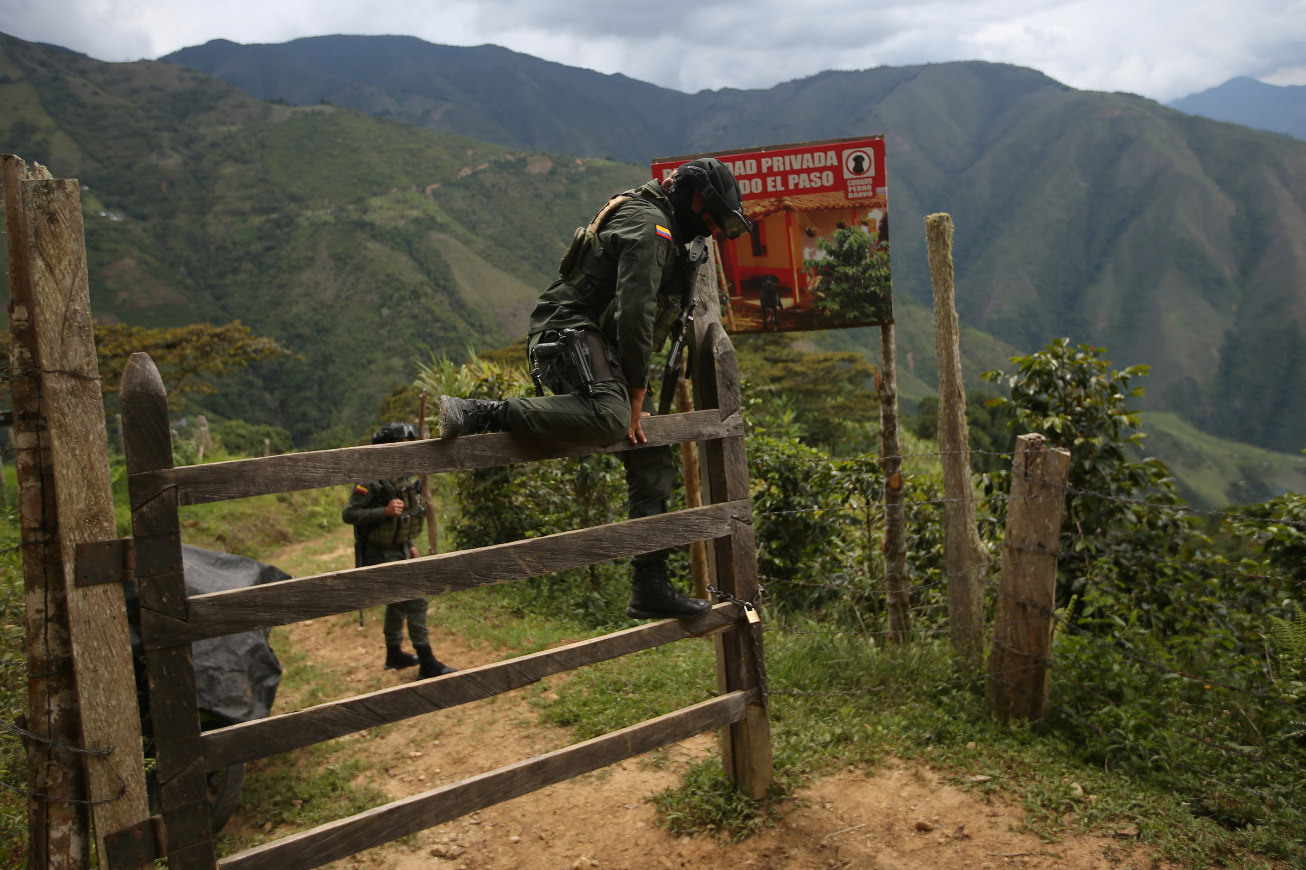 A policeman climbs over a fence to access a road that leads to an illegal mine in Buritica, Colombia April 20, 2021. Picture taken April 20, 2021. REUTERS/Luisa Gonzalez