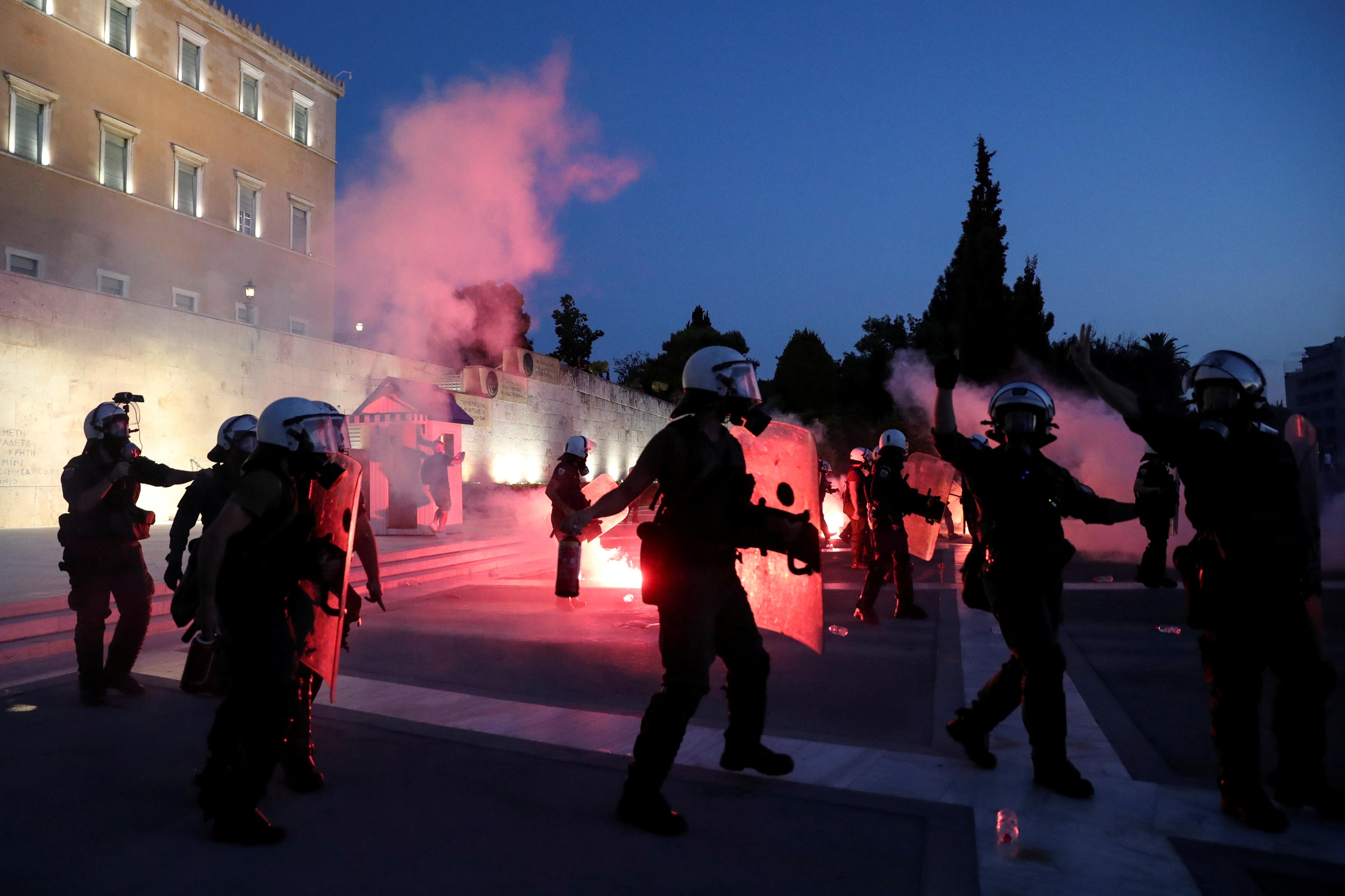 La policia antidisturbis es manté entre fum de flamarada a la tomba del soldat desconegut durant una protesta contra les vacunacions contra la malaltia del coronavirus (COVID-19) fora de l'edifici del parlament, a Atenes, Grècia, el 29 d'agost de 2021. REUTERS / Costas Baltas