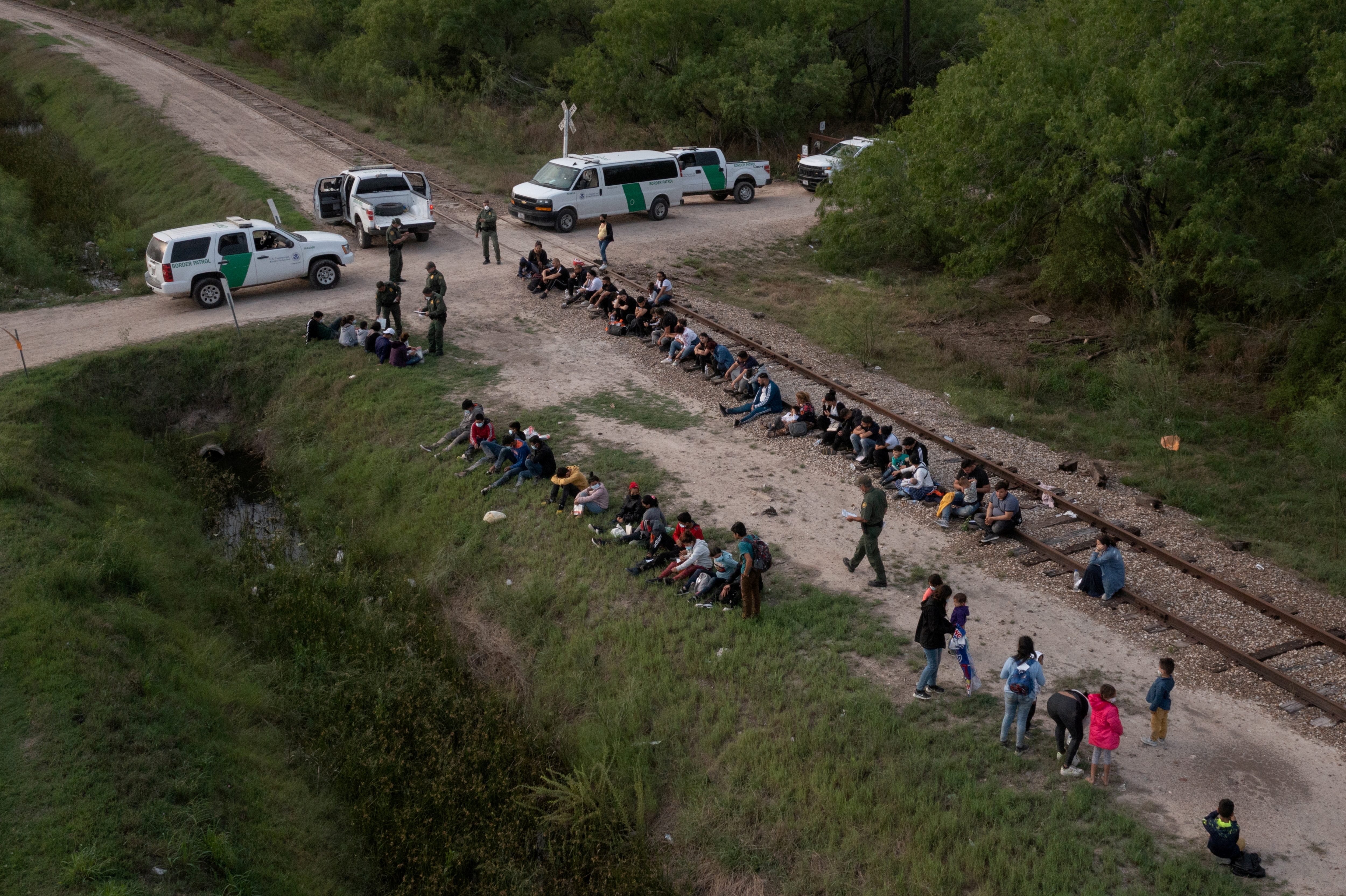 Dozens of asylum-seeking migrants from Romania, Armenia, and Central America, including a group of unaccompanied minors, await to be transported to a U.S. border patrol processing facility after crossing the Rio Grande river into the United States from Mexico on a raft in La Joya, Texas, U.S., May 5, 2021. Picture taken with a drone. REUTERS/Adrees Latif/File Photo