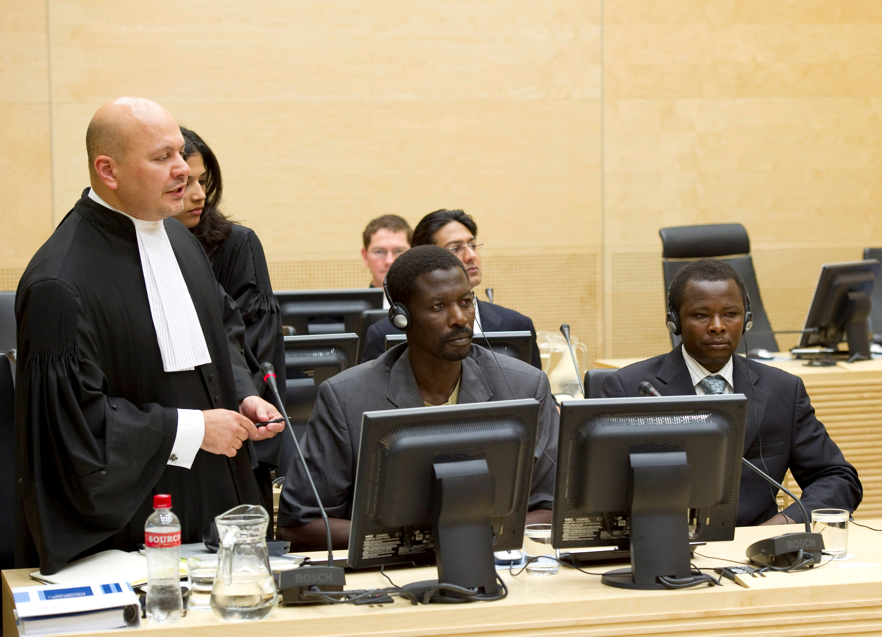 Karim Khan (L), the lawyer for Abdallah Banda Abakaer Nourain (C) and Saleh Mohammed Jerbo Jamus (R), both suspected of having committed war crimes in Darfur, speaks at the International Criminal Court in The Hague June 17, 2010. REUTERS/Toussaint Kluiters/United Photos/File Photo
