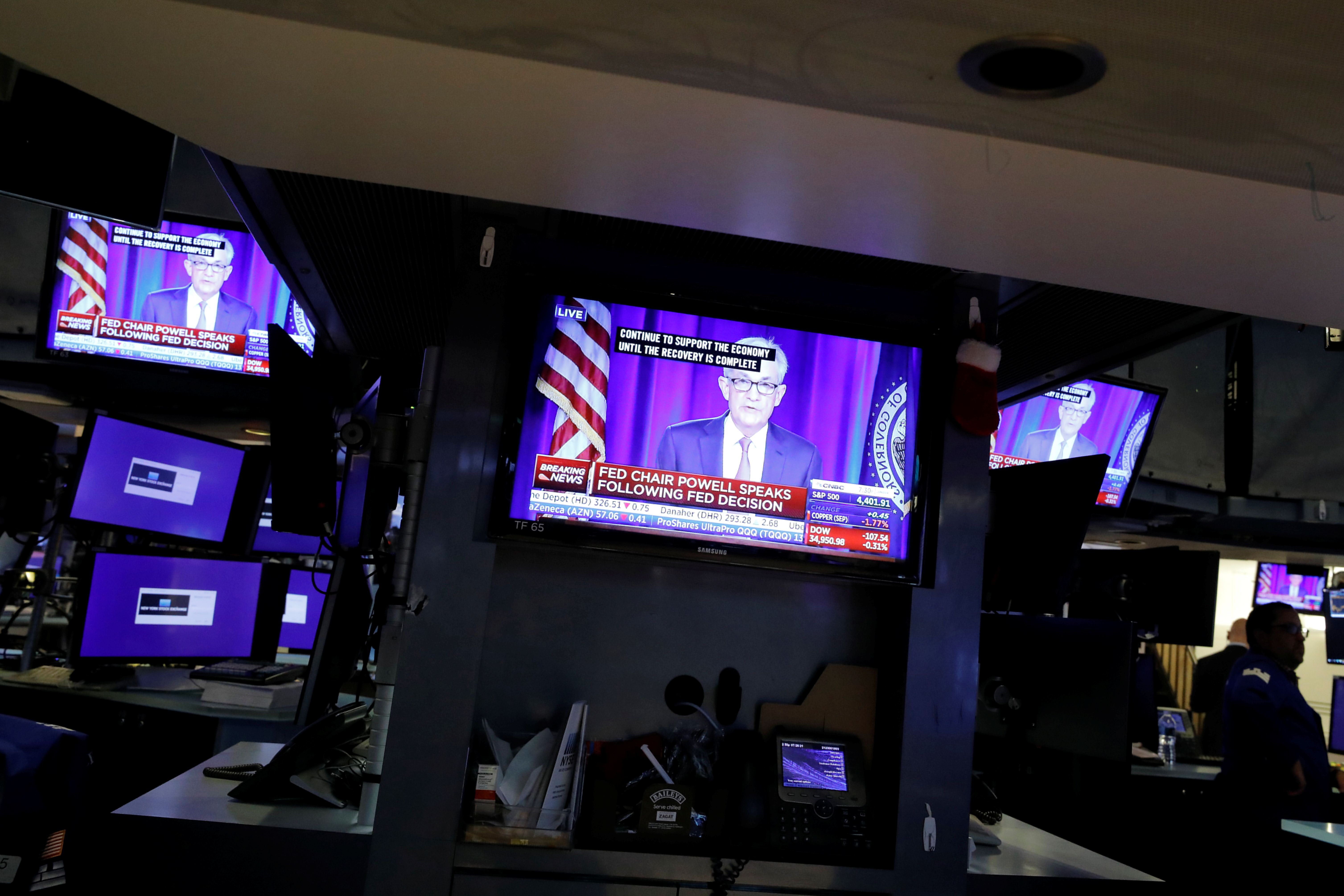 A screen displays a statement by Federal Reserve Chair Jerome Powell following the U.S. Federal Reserve's announcement as a trader works on the trading floor at New York Stock Exchange (NYSE) in New York City, New York, U.S., July 28, 2021. REUTERS/Andrew Kelly