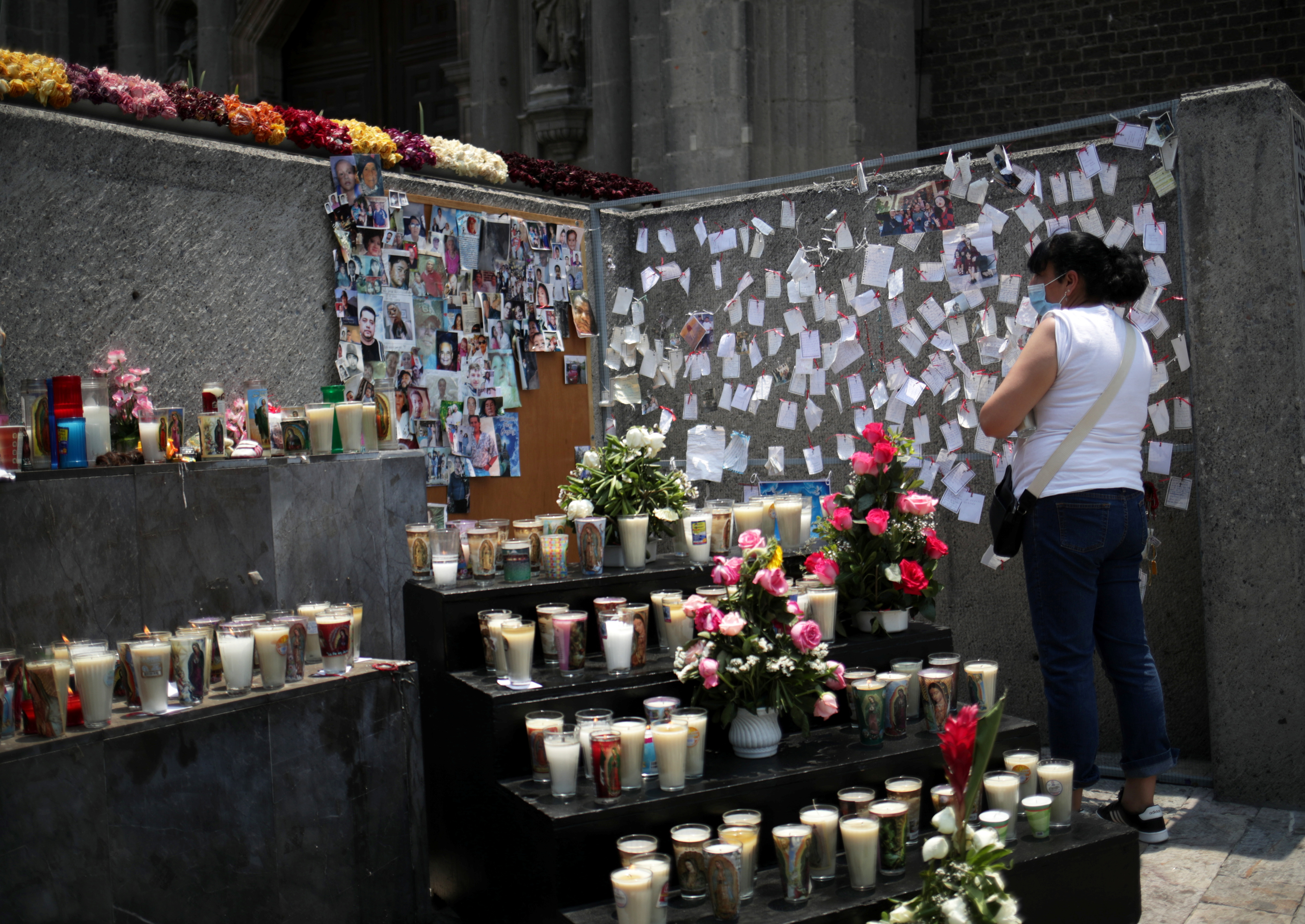 A woman visits a memorial dedicated to COVID-19 victims and other deaths in Mexico City, Mexico, April 25, 2021. Hundreds of candles, photographs, flowers and papers with messages have been placed in an area of the Basilica of Guadalupe as the outbreak continues. REUTERS/Henry Romero