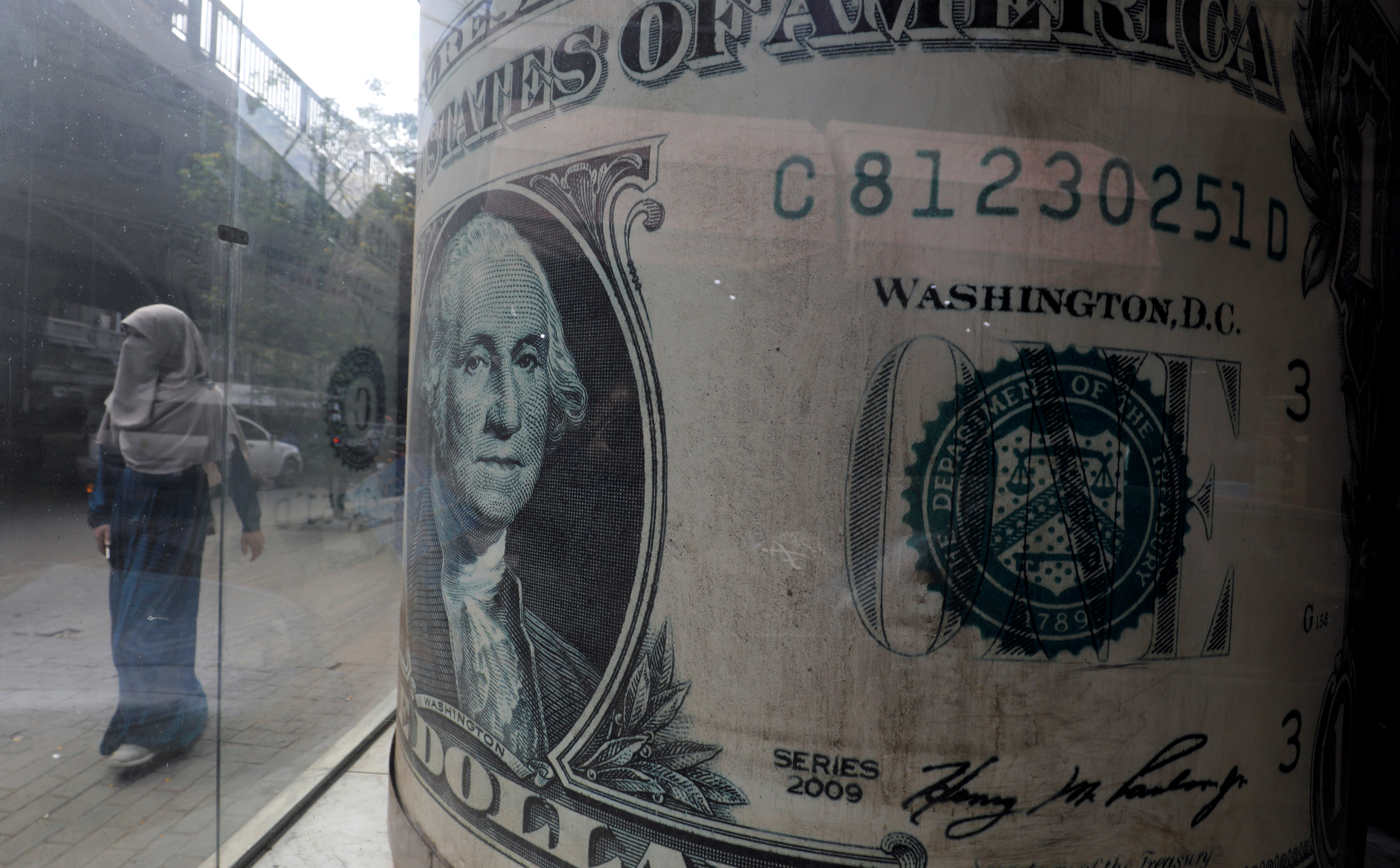 A woman wearing a full veil (niqab) walks in front of a currency exchange bureau advertisement showing an image of the U.S. dollar in Cairo, Egypt March 17, 2020. REUTERS/Amr Abdallah Dalsh/Files