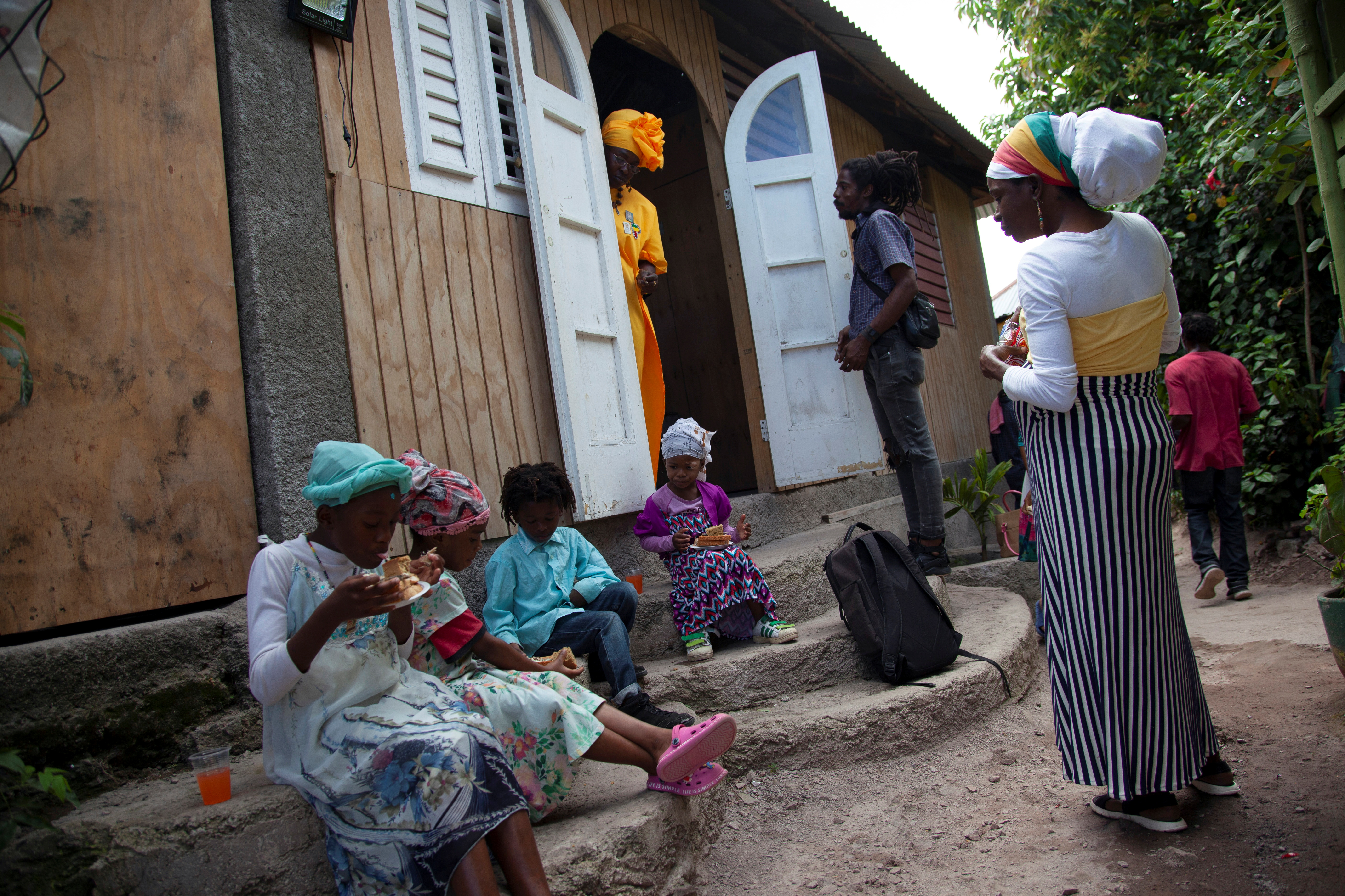 Children eat peanut butter sandwiches during the Sabbath service, at The School of Vision, a Rastafari community in the Blue Mountains, near Kingston, Jamaica, on June 19, 2021. Picture taken June 19, 2021. REUTERS/Ina Sotirova