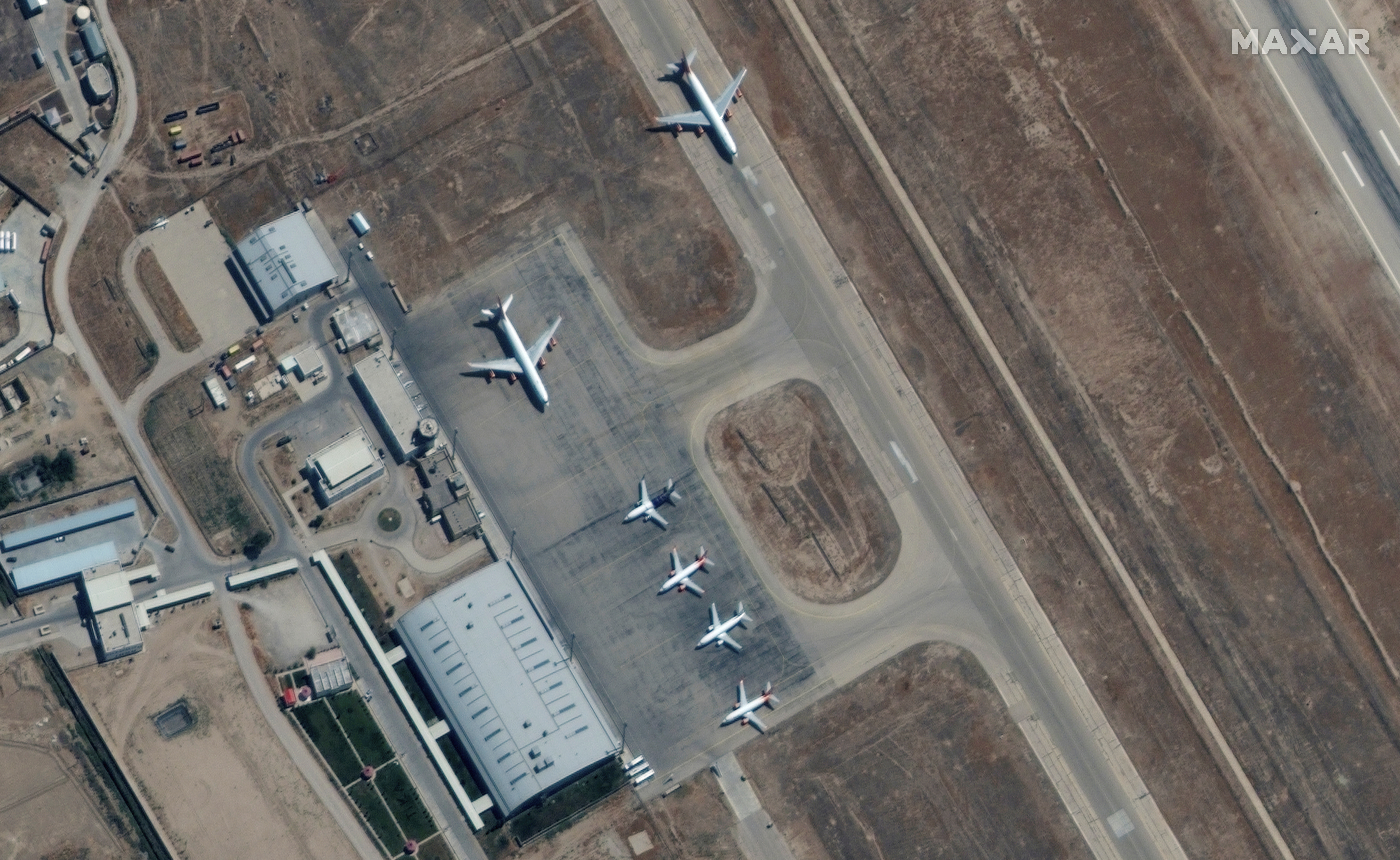 Six commercial airplanes are seen near the main terminal of the Mazar-i-Sharif airport, in northern Afghanistan, September 3 2021. Maxar Technologies/Handout via REUTERS