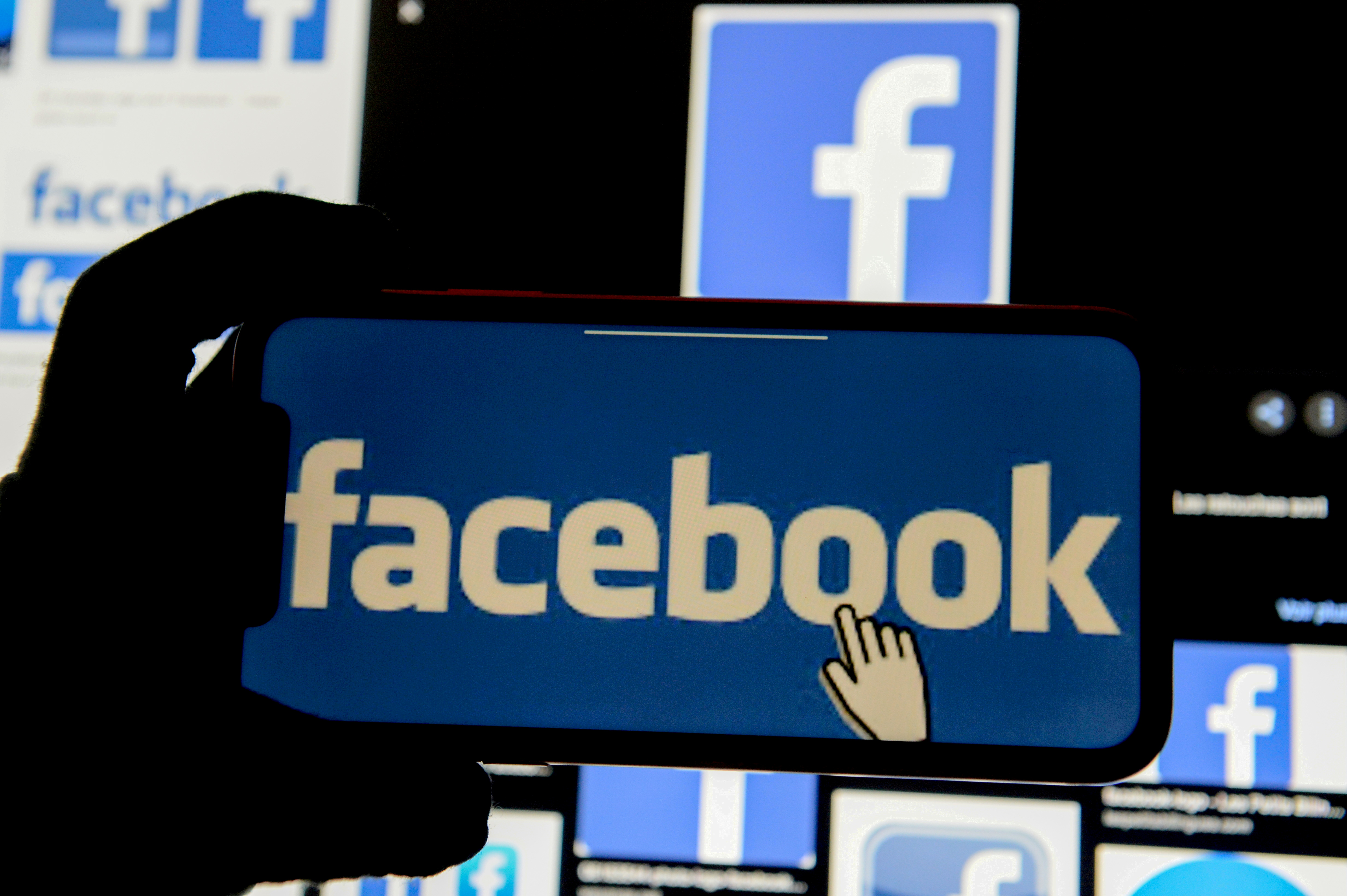 The Facebook logo is displayed on a mobile phone in this picture illustration taken December 2, 2019. REUTERS/Johanna Geron/Illustration