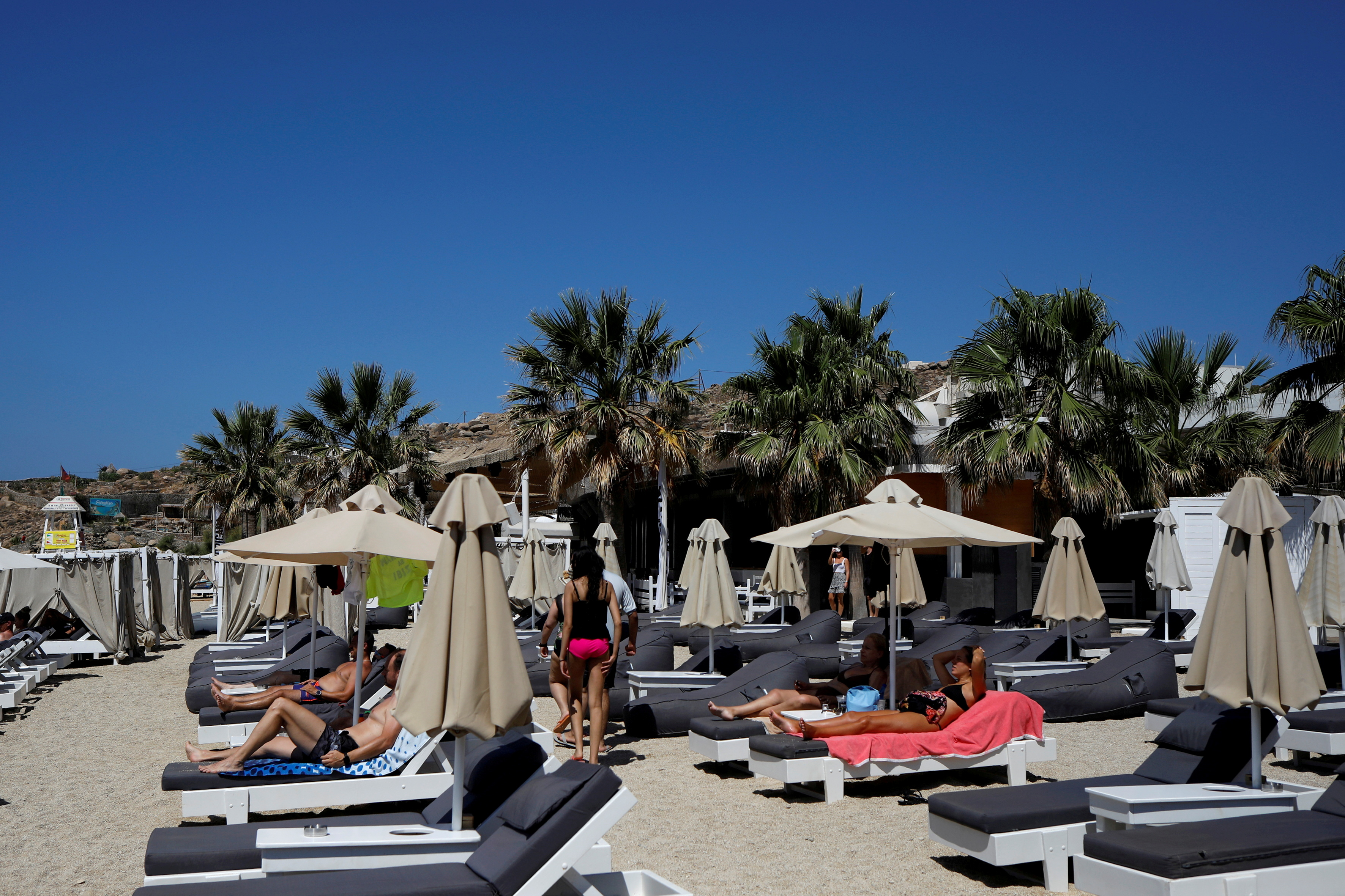 People lay on sunbeds at the Tropicana beach bar in Paradise beach on the island of Mykonos, Greece, July 18, 2021. REUTERS/Louiza Vradi/File Photo