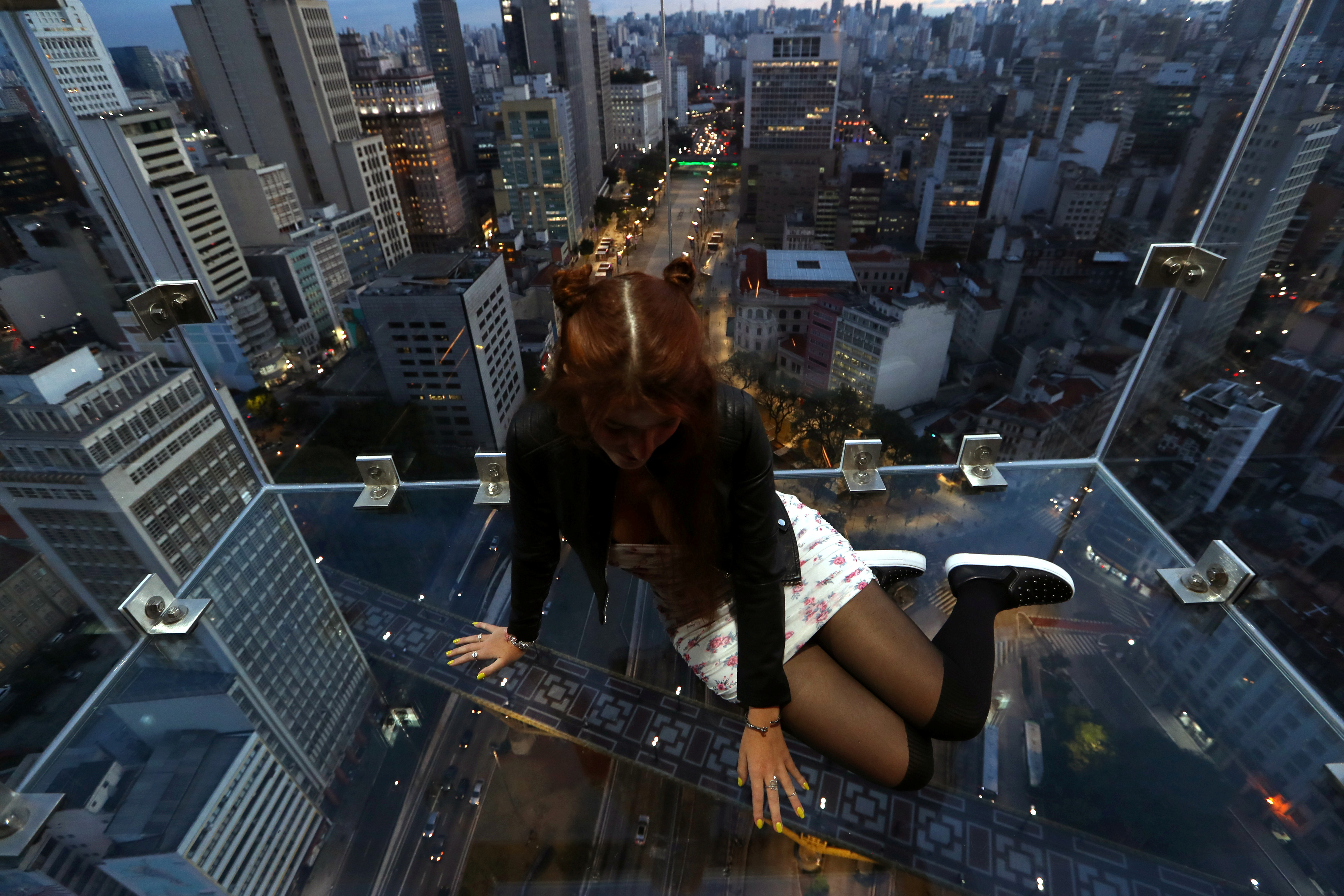 Influencer Marcella Nery sits inside Sampa Sky, a reinforced glass box that protrudes beyond the building and allows to see not only the horizon, but also the ground below your feet, in downtown Sao Paulo, Brazil, August 3, 2021. REUTERS/Amanda Perobelli