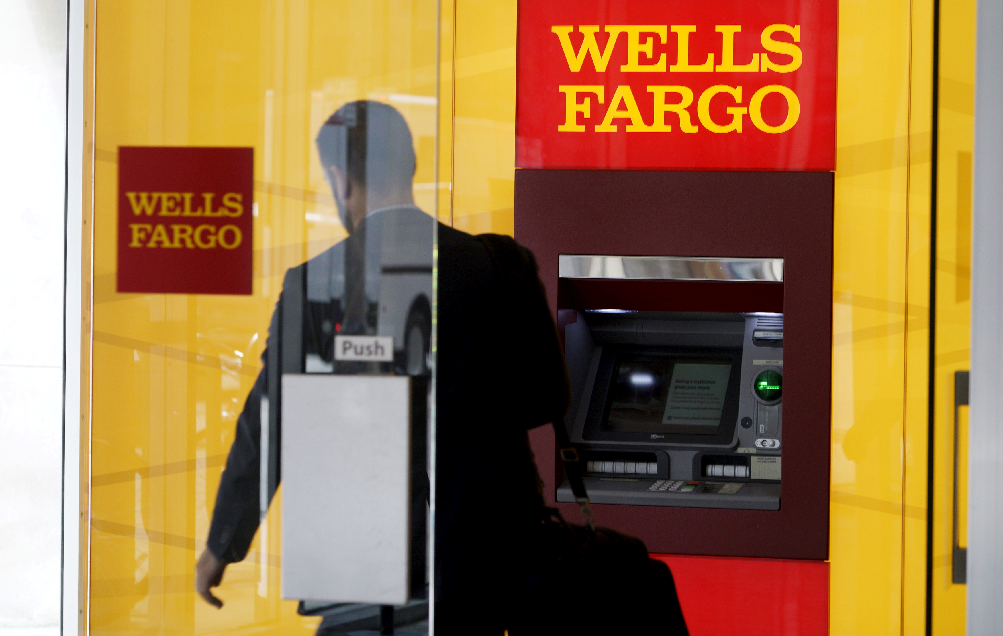 A man walks by an ATM at the Wells Fargo & Co. bank in downtown Denver April 13, 2016.  REUTERS/Rick Wilking/File Photo