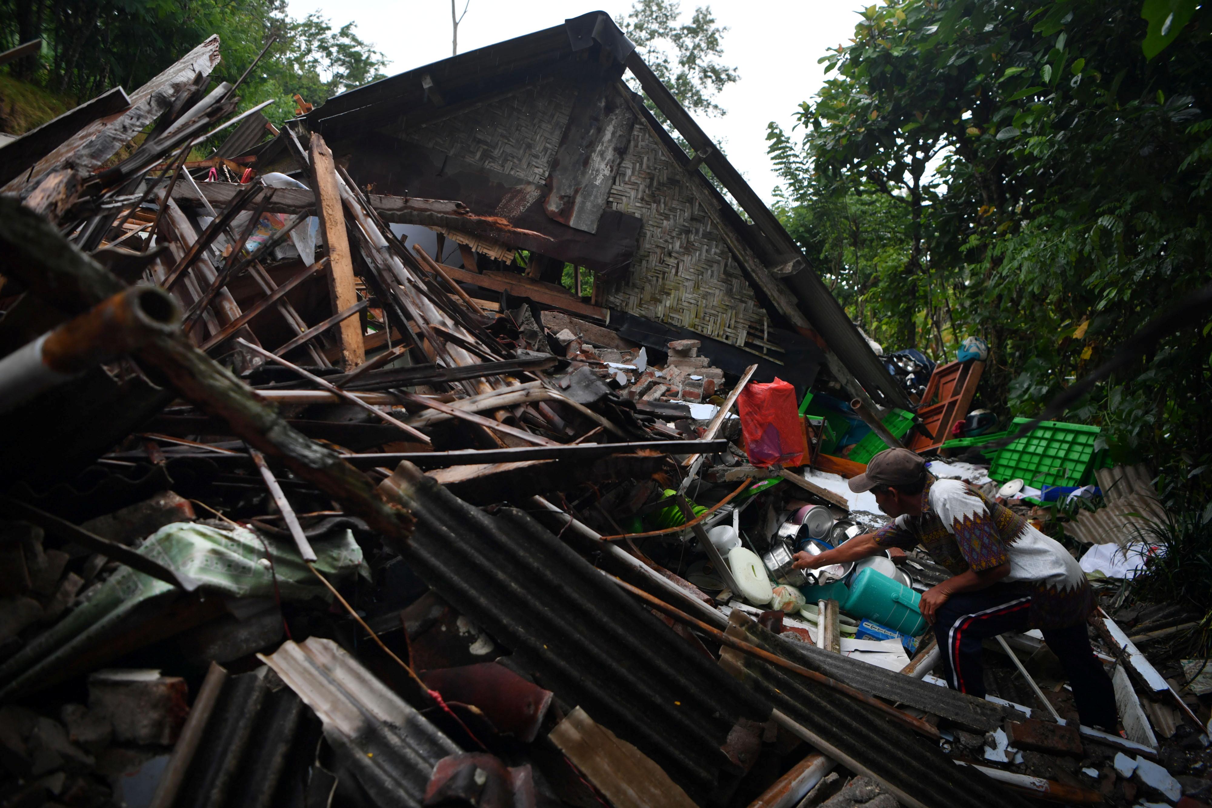 A man salvages his belongings at a house damaged by an earthquake in Lumajang, East Java province, Indonesia April 11, 2021, in this photo taken by Antara Foto. Antara Foto/Zabur Karuru/via REUTERS