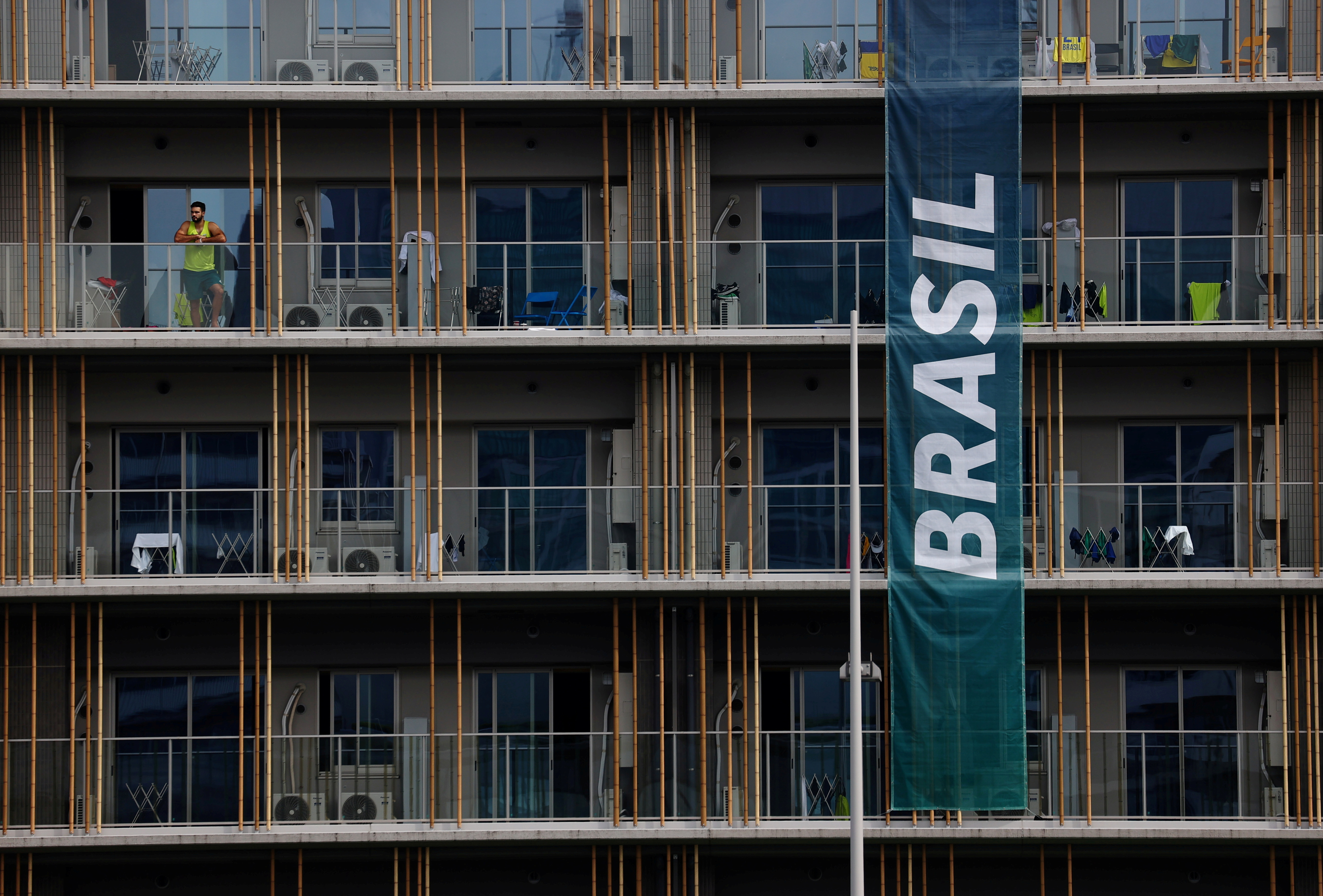 A man stands on a balcony at the athletes' village for Tokyo 2020 Olympic Games in Tokyo, Japan, July 29, 2021.   REUTERS/Kim Kyung-Hoon