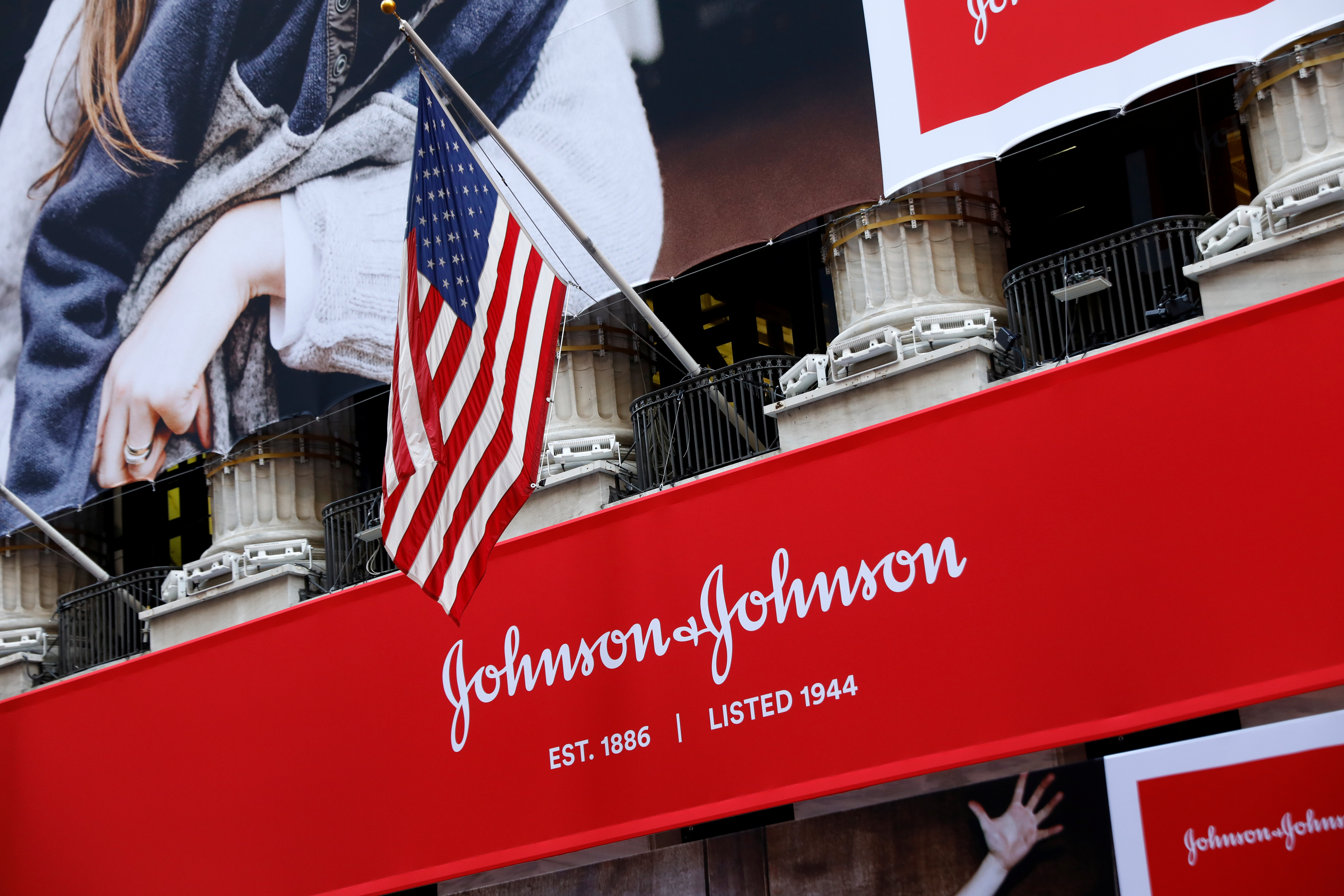 The U.S. flag is seen over the company logo for Johnson & Johnson to celebrate the 75th anniversary of the company's listing at the New York Stock Exchange (NYSE) in New York, U.S., September 17, 2019. REUTERS/Brendan McDermid