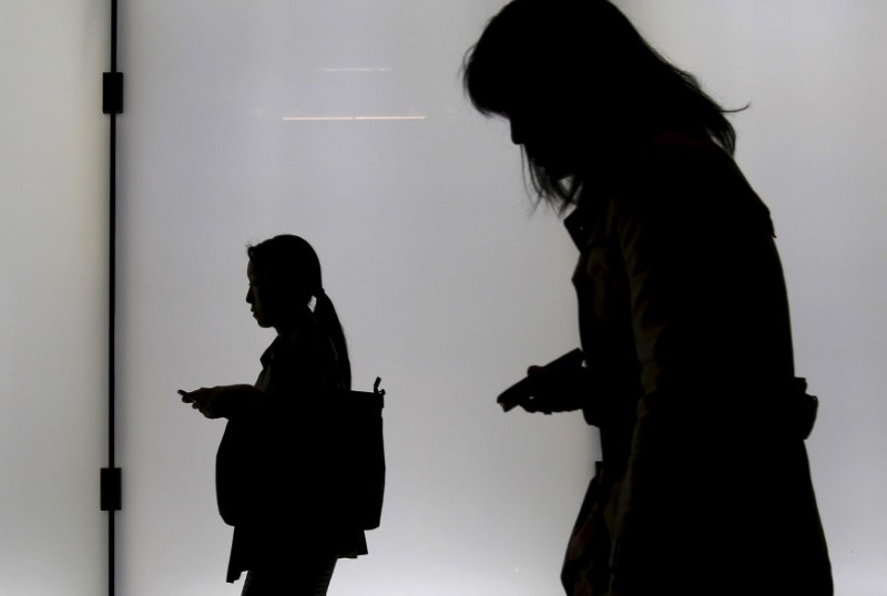 Women holding their mobile phones are silhouetted as they walk on an overpass at a business district in Tokyo, Japan, November 5, 2015. REUTERS/Yuya Shino