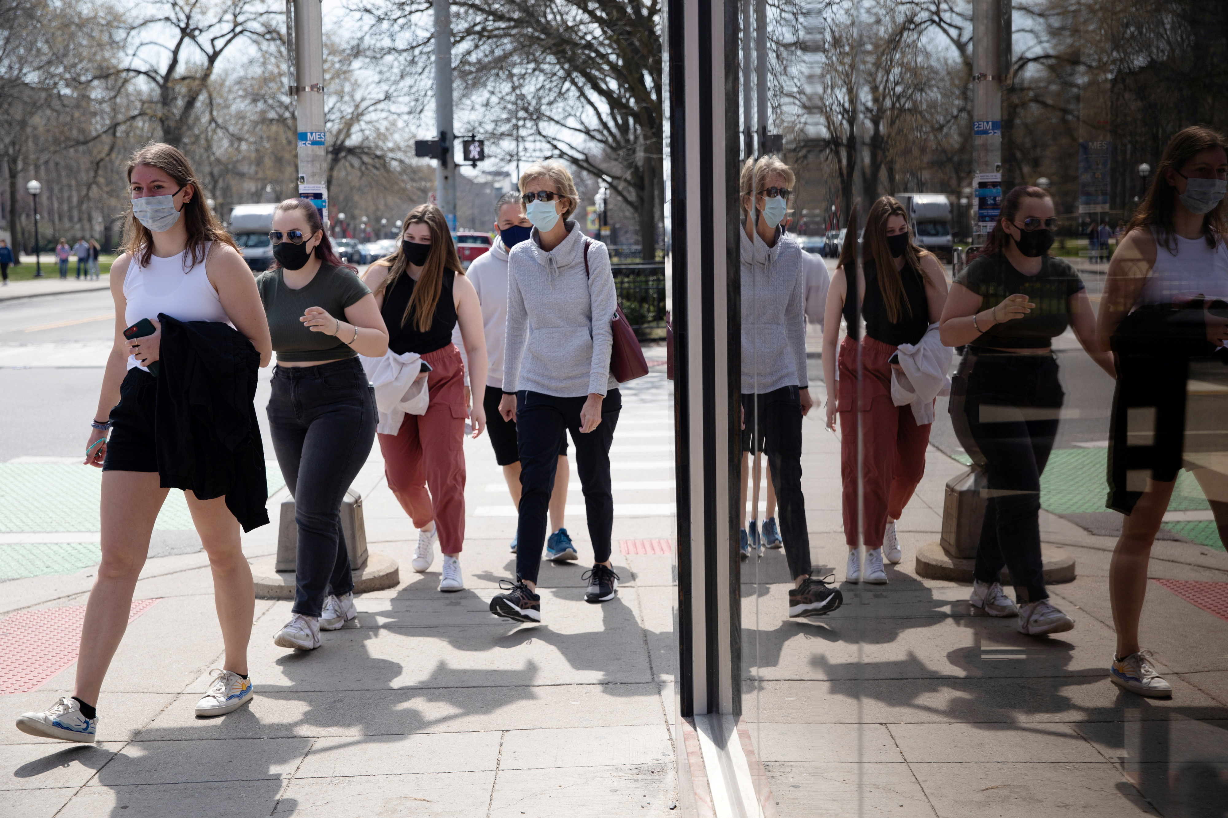 A group of people walk wearing protective masks head to a restaurant as coronavirus disease (COVID-19) restrictions are eased in Ann Arbor, Michigan, U.S., April 4, 2021.  REUTERS/Emily Elconin/File Photo