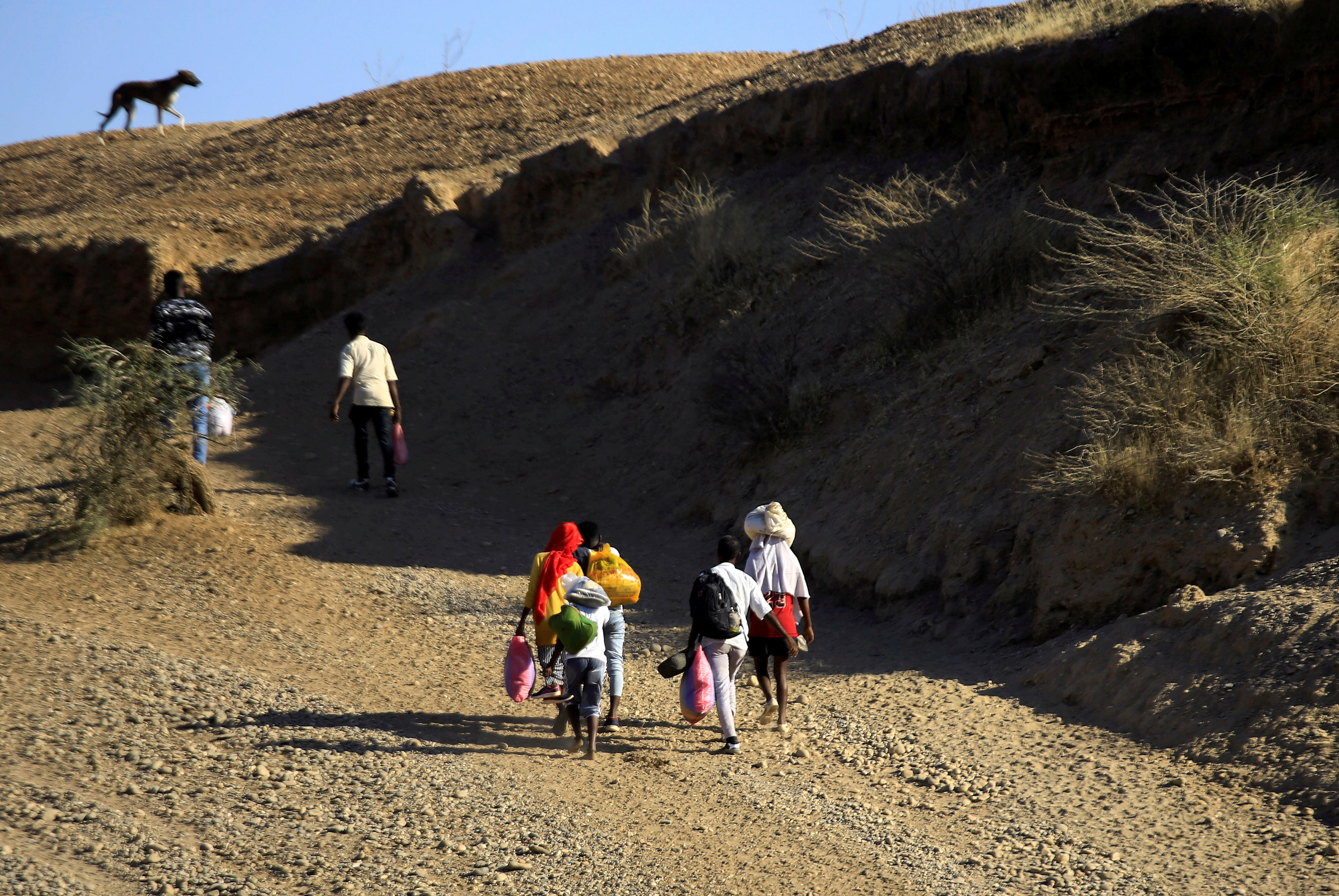 Ethiopians, who fled the ongoing fighting in Tigray region, carry their belongings after crossing the Setit River on the Sudan-Ethiopia border, in the eastern Kassala state, Sudan December 16, 2020. REUTERS/Mohamed Nureldin Abdallah/File Photo