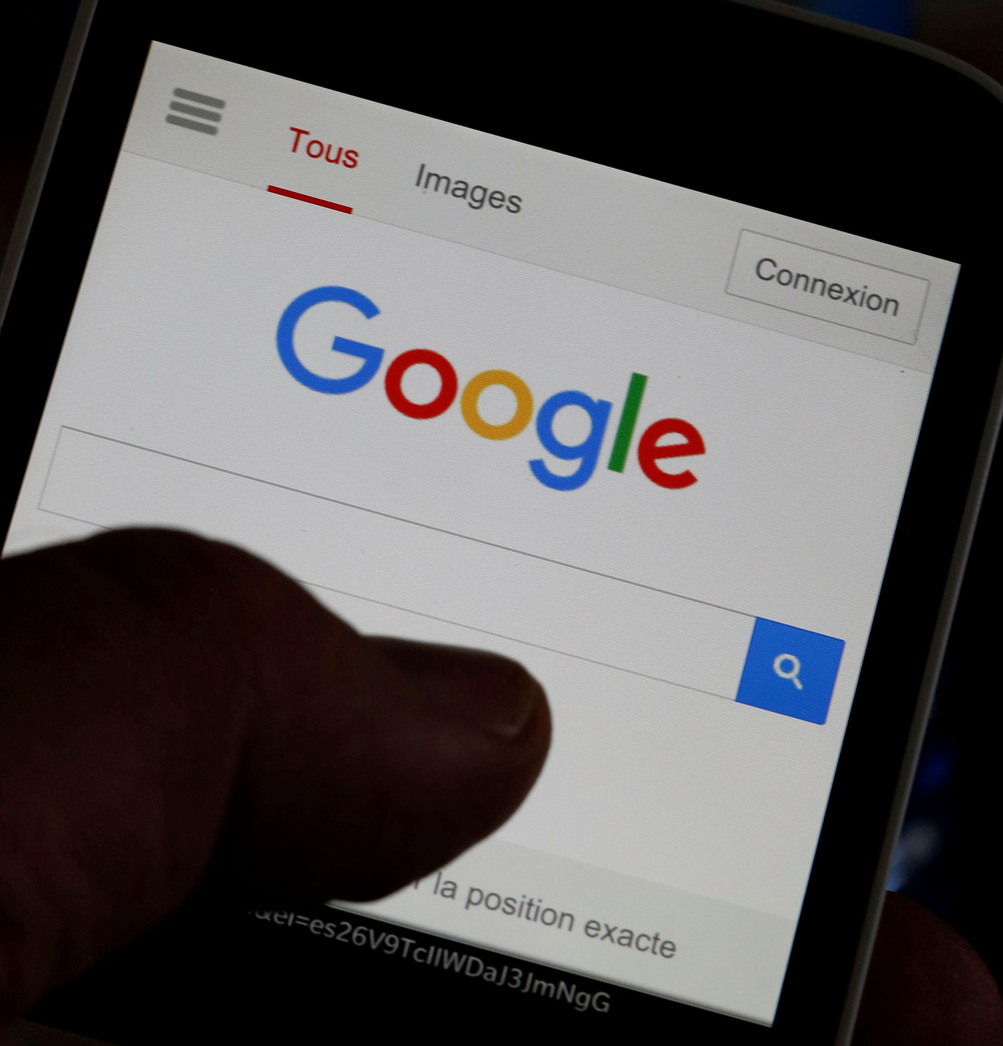 A man holds his smartphone which displays the Google home page, in this picture illustration taken in Bordeaux, Southwestern France, August 22, 2016. REUTERS/Regis Duvignau/Files