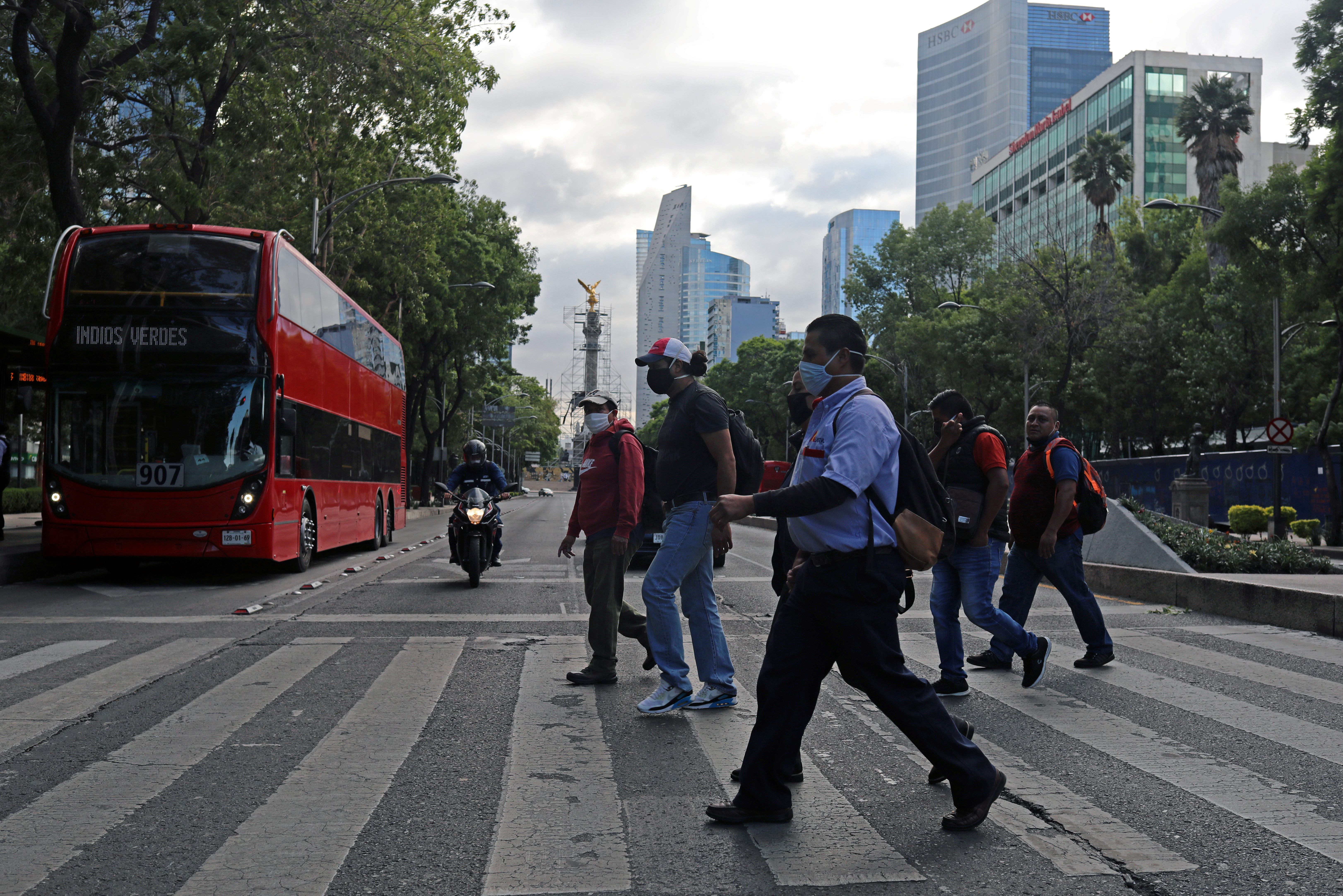 People cross Reforma Avenue as the mayor of Mexico City said on Friday that the Mexican capital will lift restrictions on car traffic and public transport next week, allowing 340,000 factory workers to get back to work, even though new cases of coronavirus disease (COVID-19) are still rising, in Mexico City, Mexico June 12, 2020. REUTERS/Henry Romero