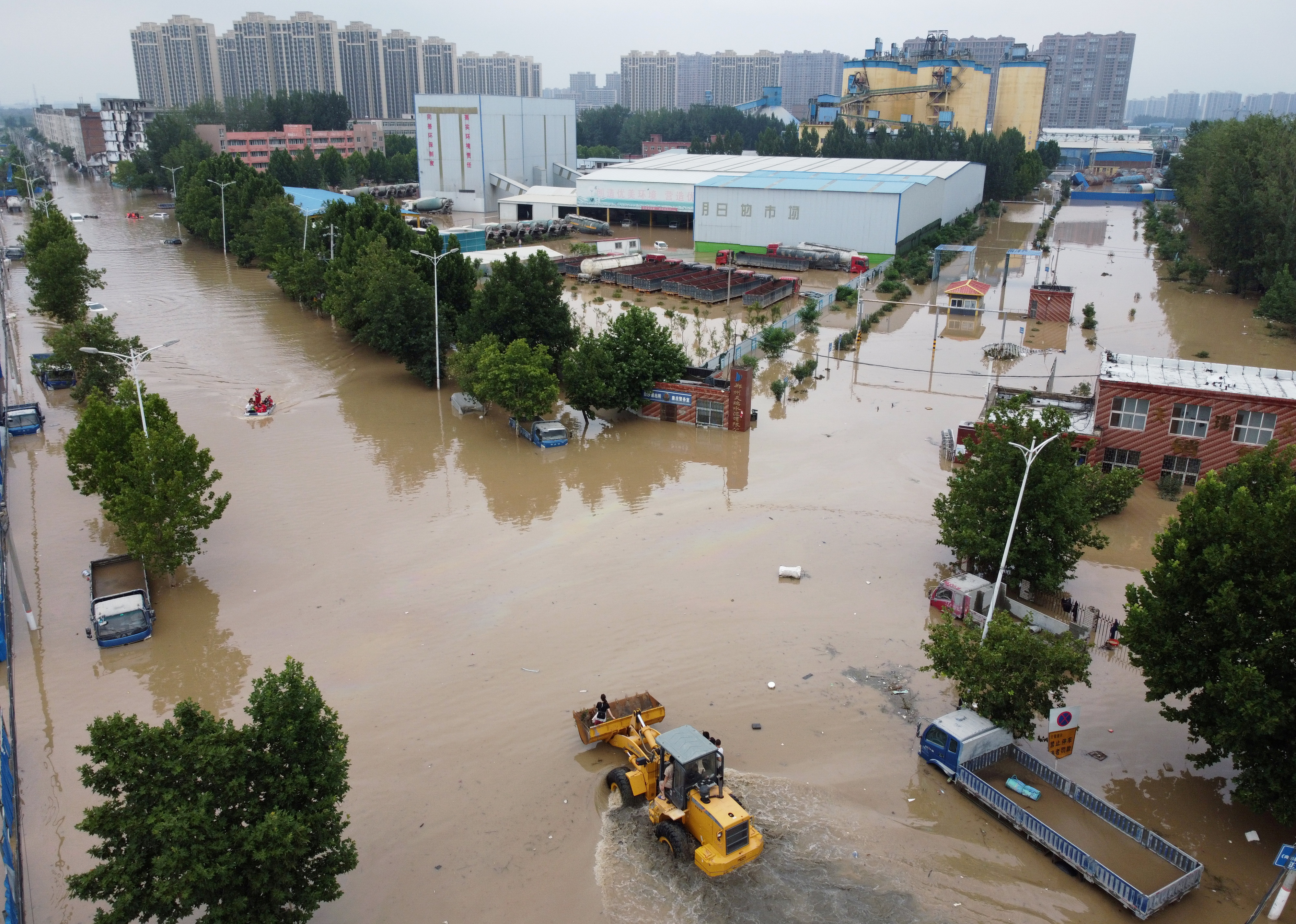 An aerial view shows rescue workers evacuating residents on a flooded road following heavy rainfall in Zhengzhou, Henan province, China July 22, 2021. Picture taken with a drone.  REUTERS/Aly Song/File Photo