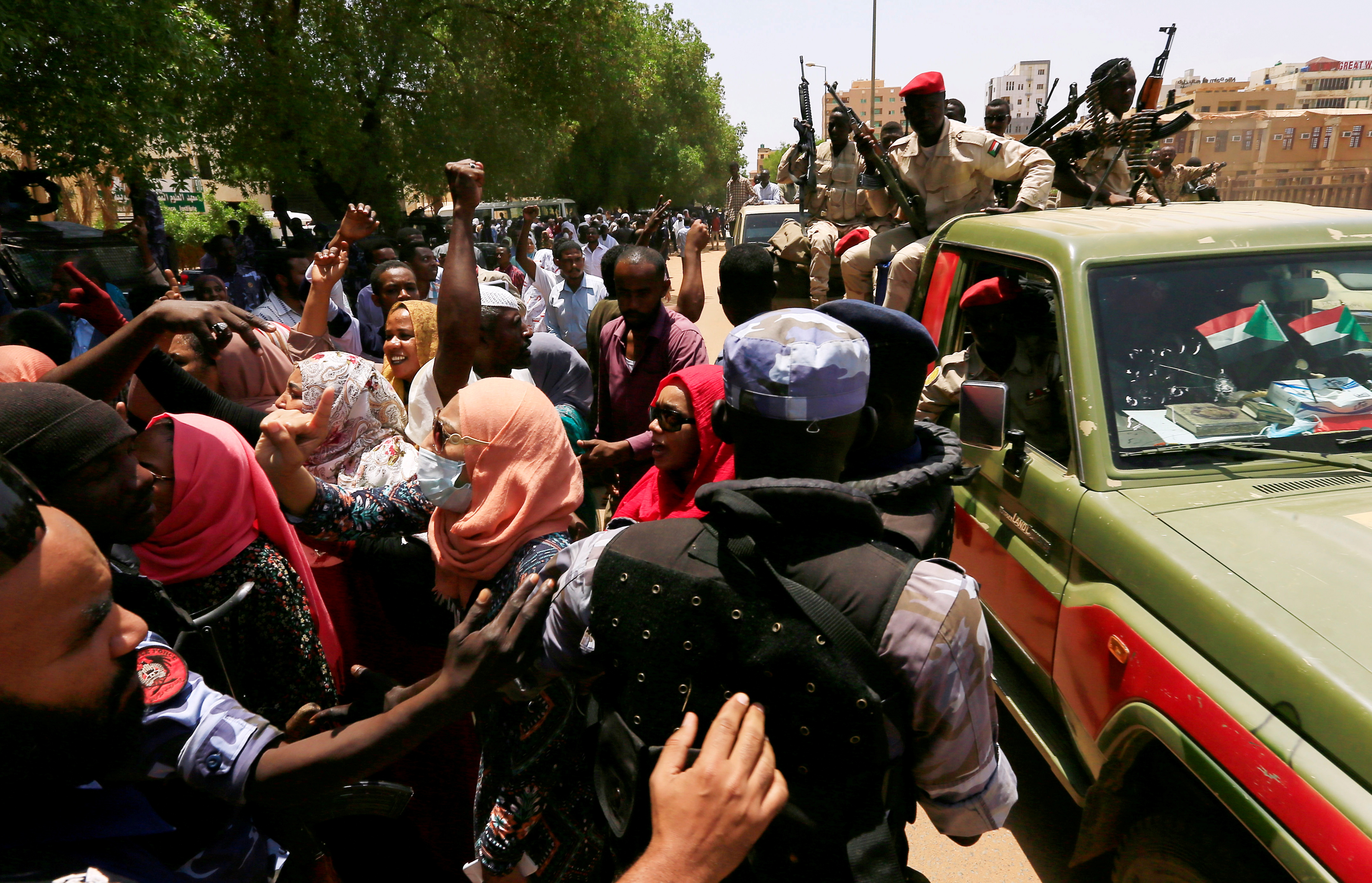 Sudanese citizens attempt to cross a police blockade as they chant slogans outside the court during the new trial against ousted President Omar al-Bashir and some of his former allies on charges of leading a military coup that brought the autocrat to power in 1989, in Khartoum, Sudan September 1, 2020. REUTERS/Mohamed Nureldin Abdallah/File Photo
