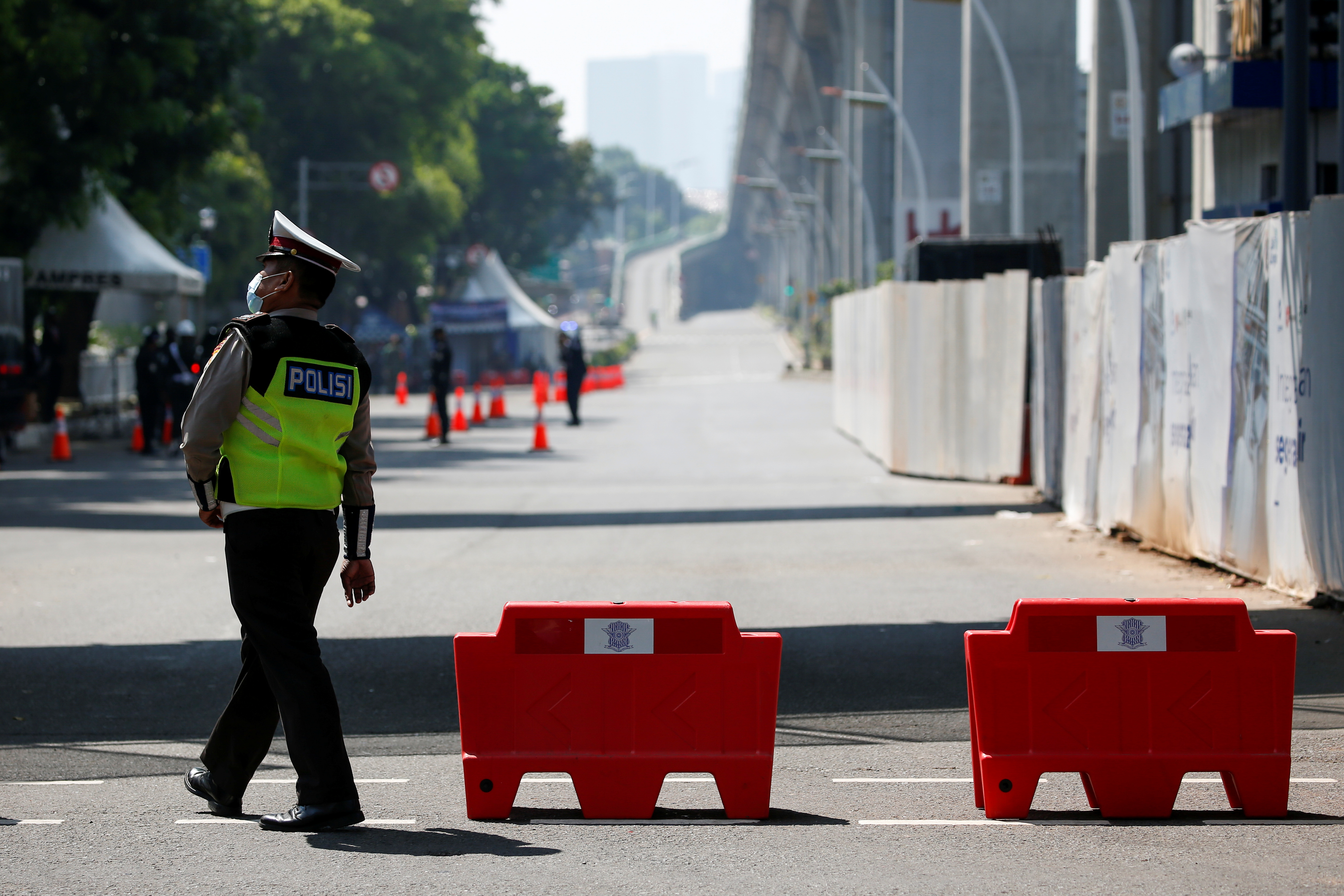 A police officer walks as he guards outside the Association of Southeast Asian Nations (ASEAN) secretariat building, before the ASEAN leaders' meeting in Jakarta, Indonesia, April 24, 2021. REUTERS/Willy Kurniawan
