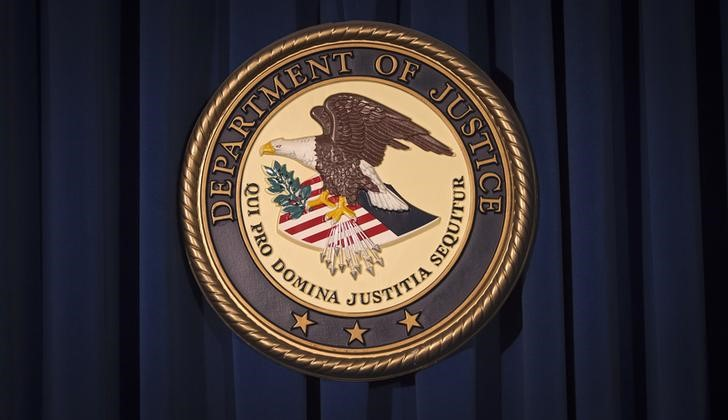 : The Department of Justice (DOJ) logo is pictured on a wall after a news conference to discuss alleged fraud by Russian Diplomats in New York December 5, 2013.     REUTERS/Carlo Allegri
