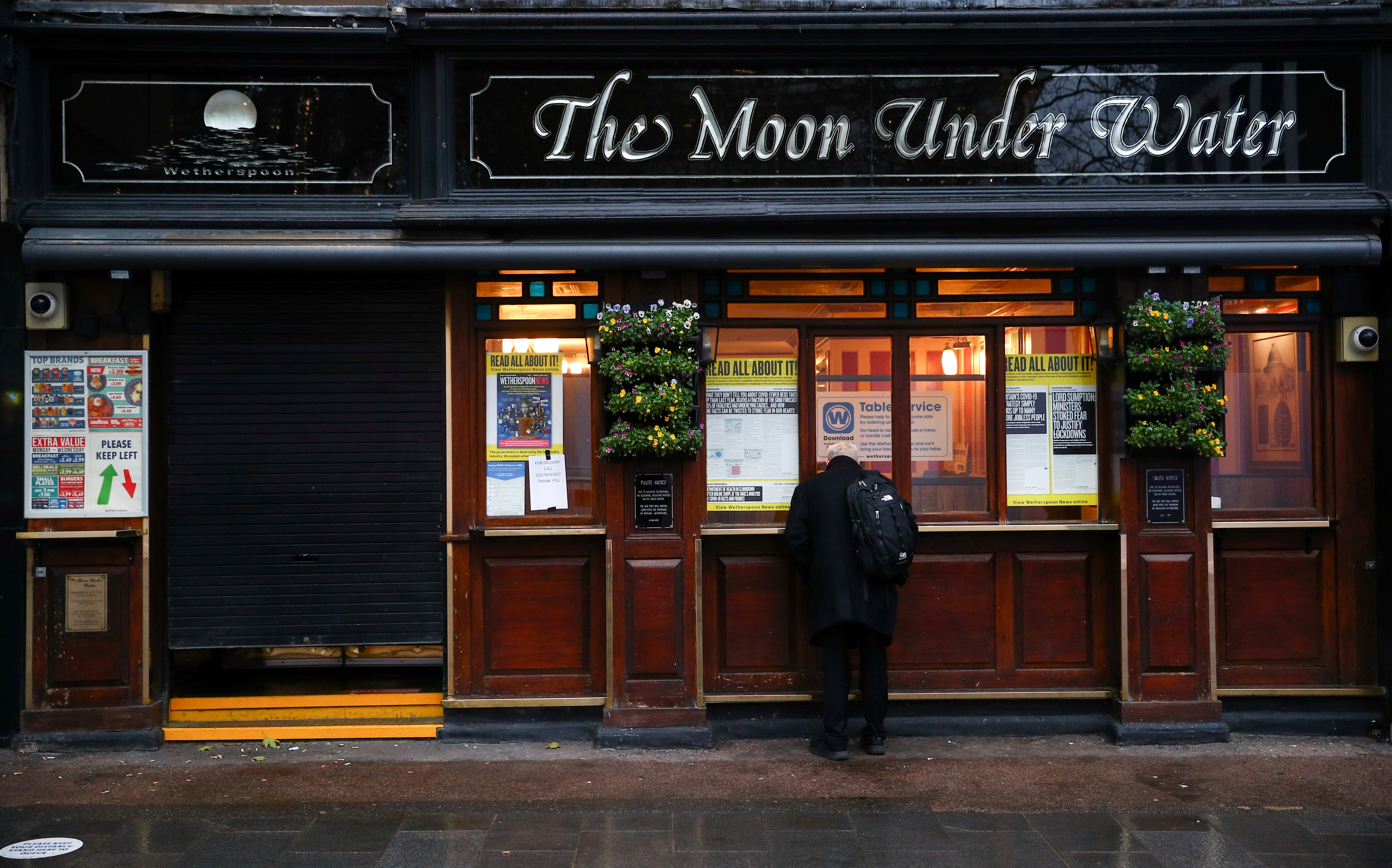 A man stands outside a closed pub, amid the coronavirus disease (COVID-19) outbreak, in London, Britain December 16, 2020. REUTERS/Hannah Mckay/File Photo