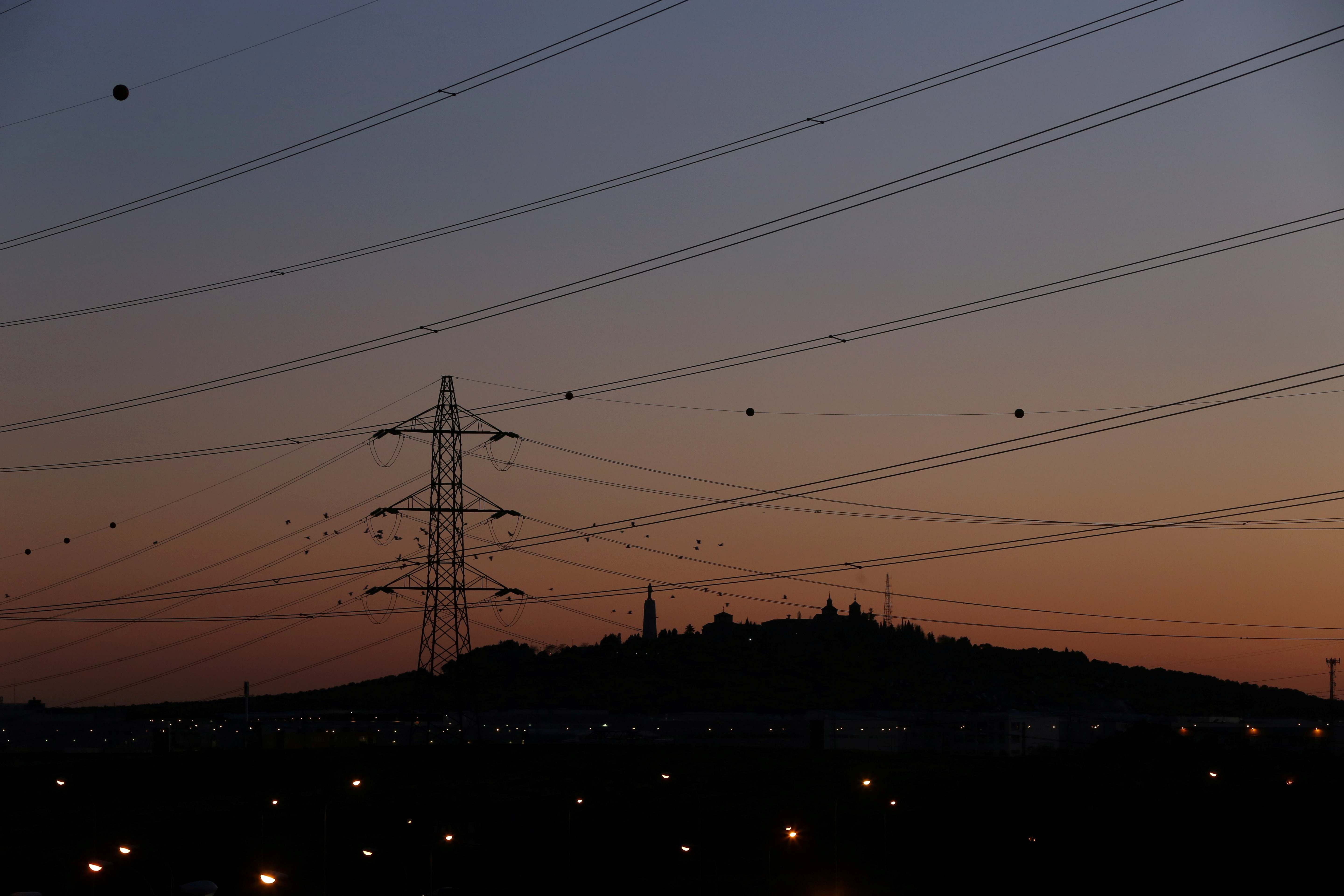 Power lines connecting pylons of high-tension electricity are seen at sunset outside Madrid, Spain January 24, 2017. REUTERS/Susana Vera