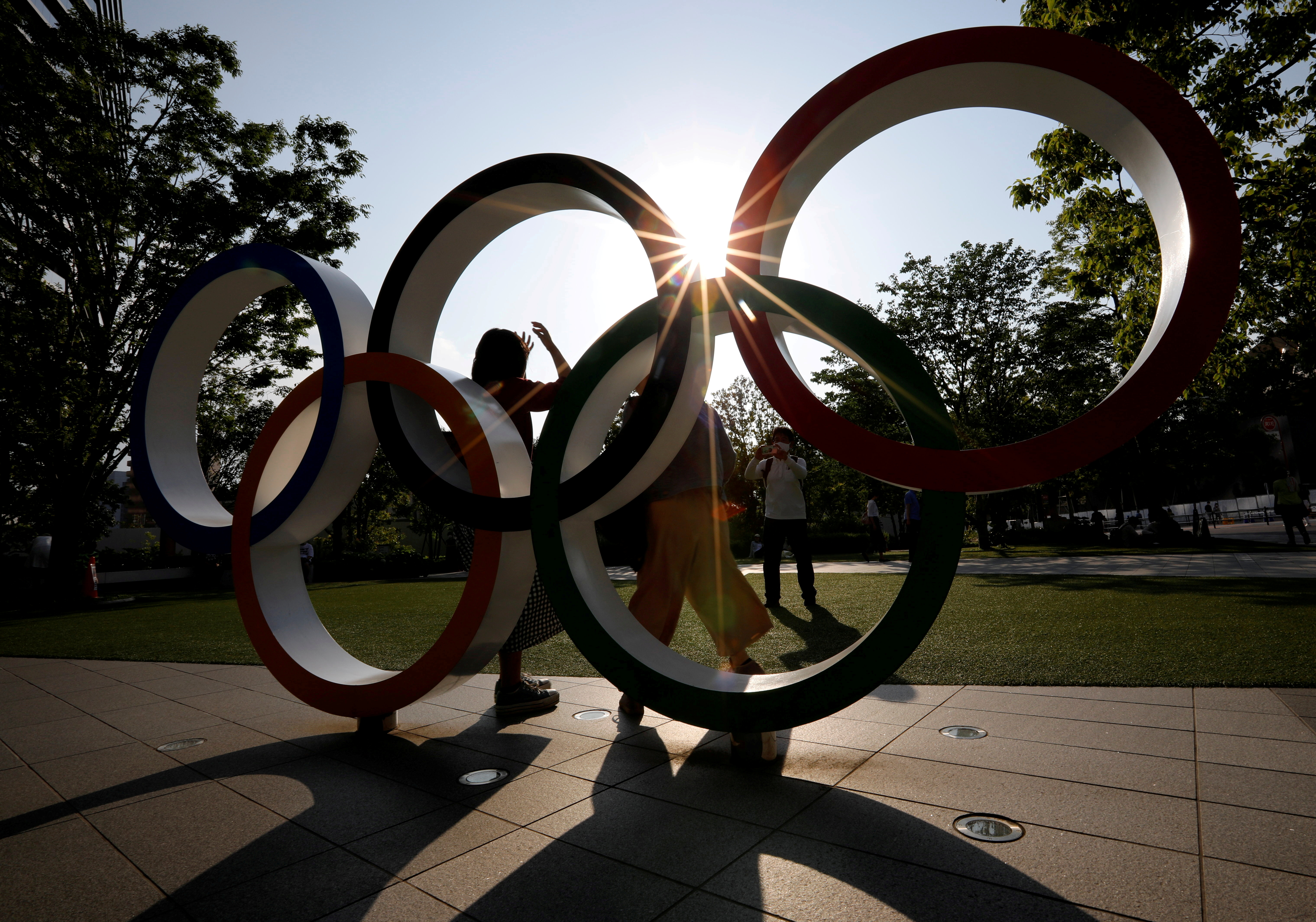 Visitors try to take photos in front of the Olympic Rings monument outside the Japan Olympic Committee (JOC) headquarters near the National Stadium, the main stadium for the 2020 Tokyo Olympic Games that have been postponed to 2021 due to the coronavirus disease (COVID-19) outbreak, in Tokyo, Japan May 30, 2021.  REUTERS/Issei Kato/File Photo