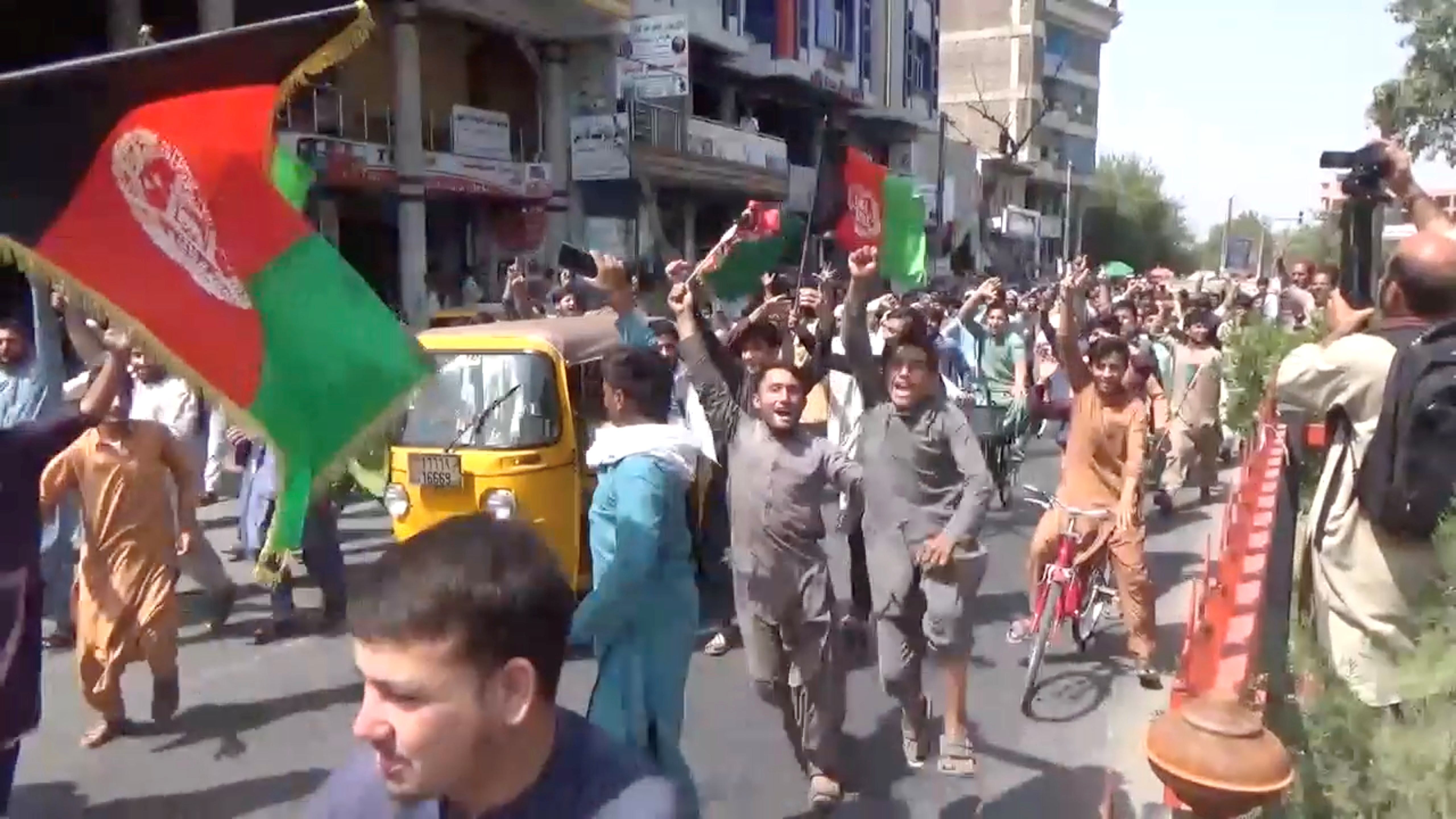 People carry Afghan flags as they take part in an anti-Taliban protest in Jalalabad, Afghanistan August 18, 2021 in this screen grab taken from a video. Pajhwok Afghan News/Handout via REUTERS