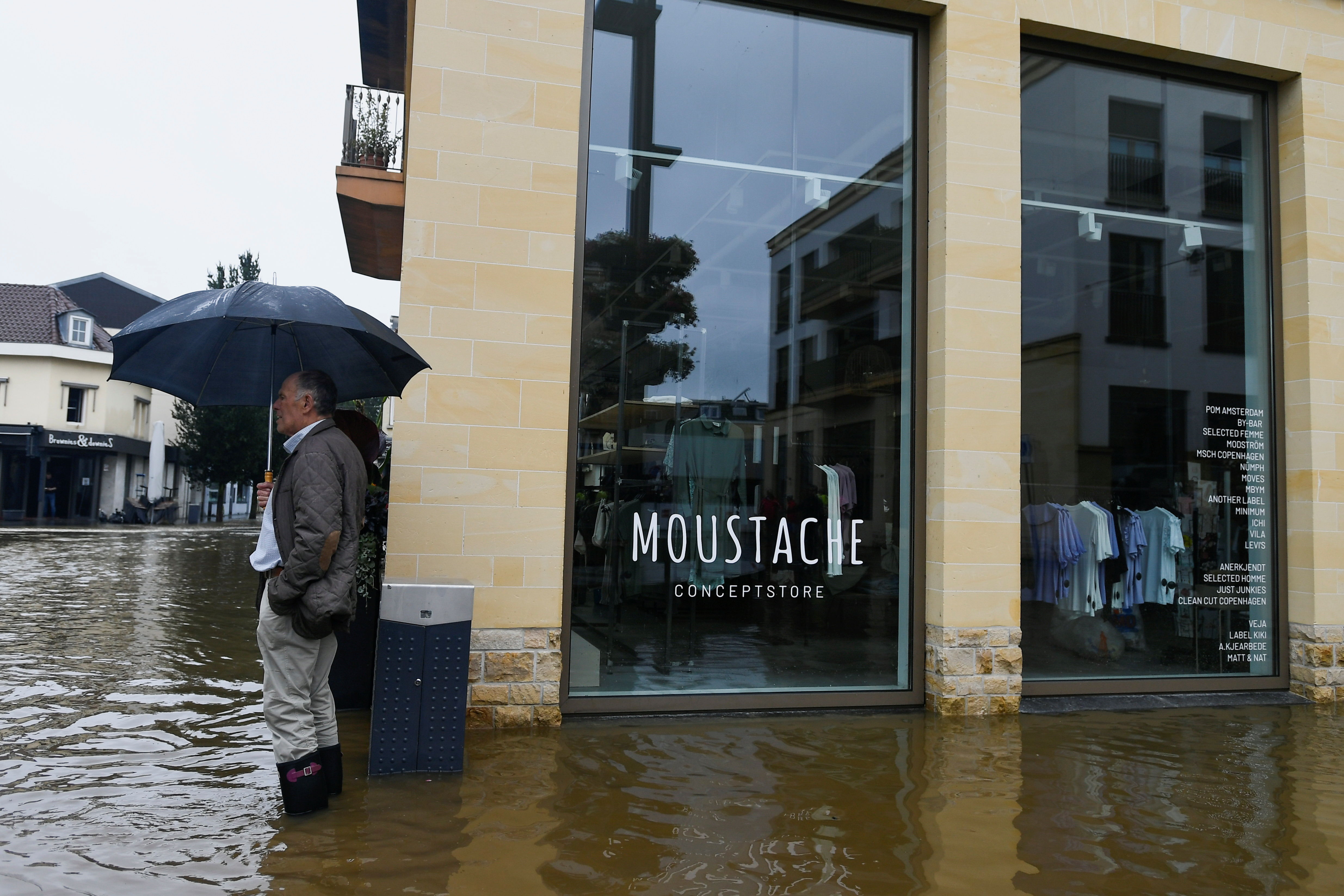 A man with an umbrella stands at a flooded street, following heavy rainfalls in Valkenburg, Netherlands, July 15, 2021. REUTERS/Piroschka Van De Wouw