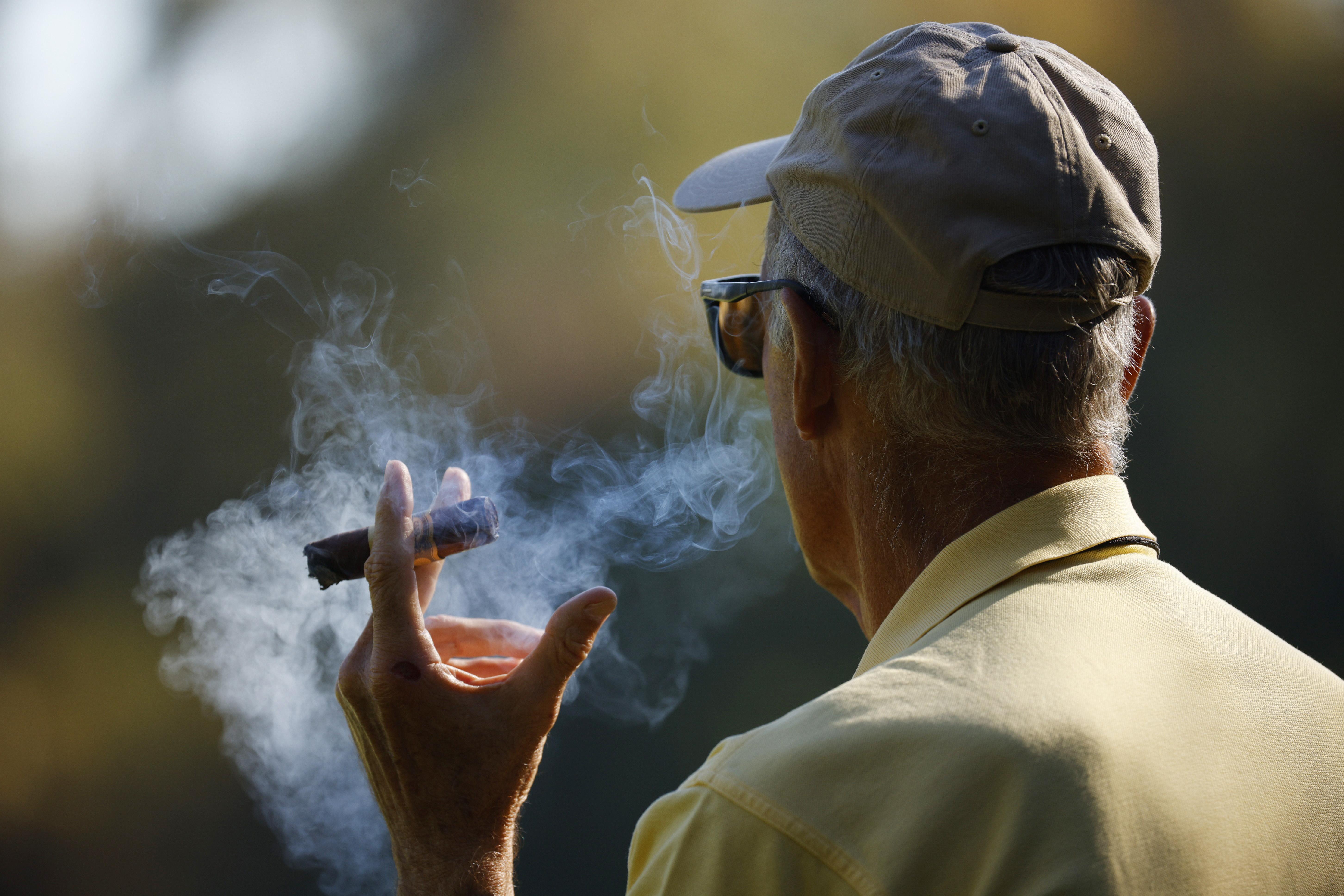 A spectator smokes a cigar in Augusta, Georgia, U.S., November 13, 2020. REUTERS/Brian Snyder