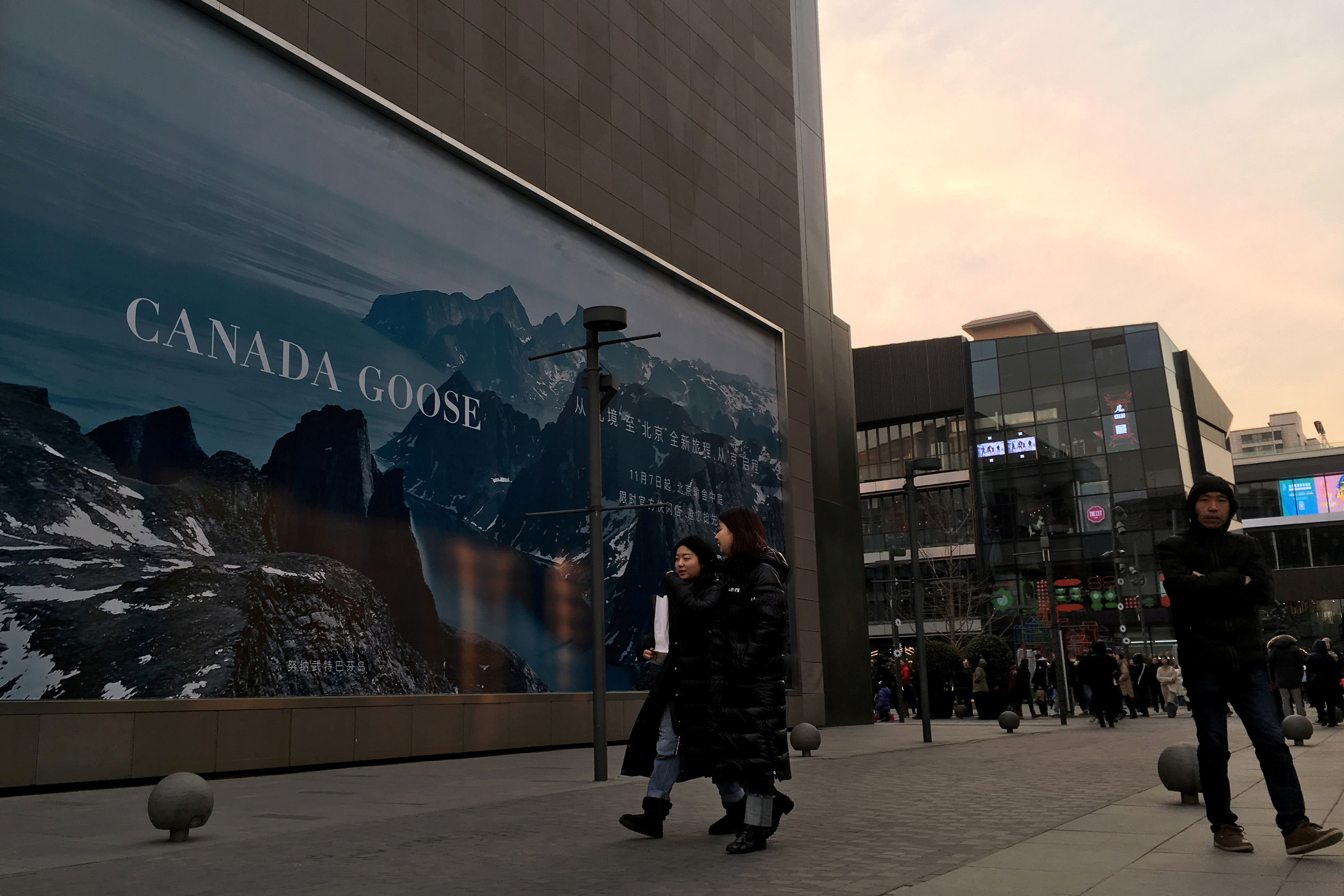 People walk past an advertisement near the flagship store of Canadian luxury parka maker Canada Goose, in Sanlitun area of Beijing, China December 31, 2018. REUTERS/Martin Pollard