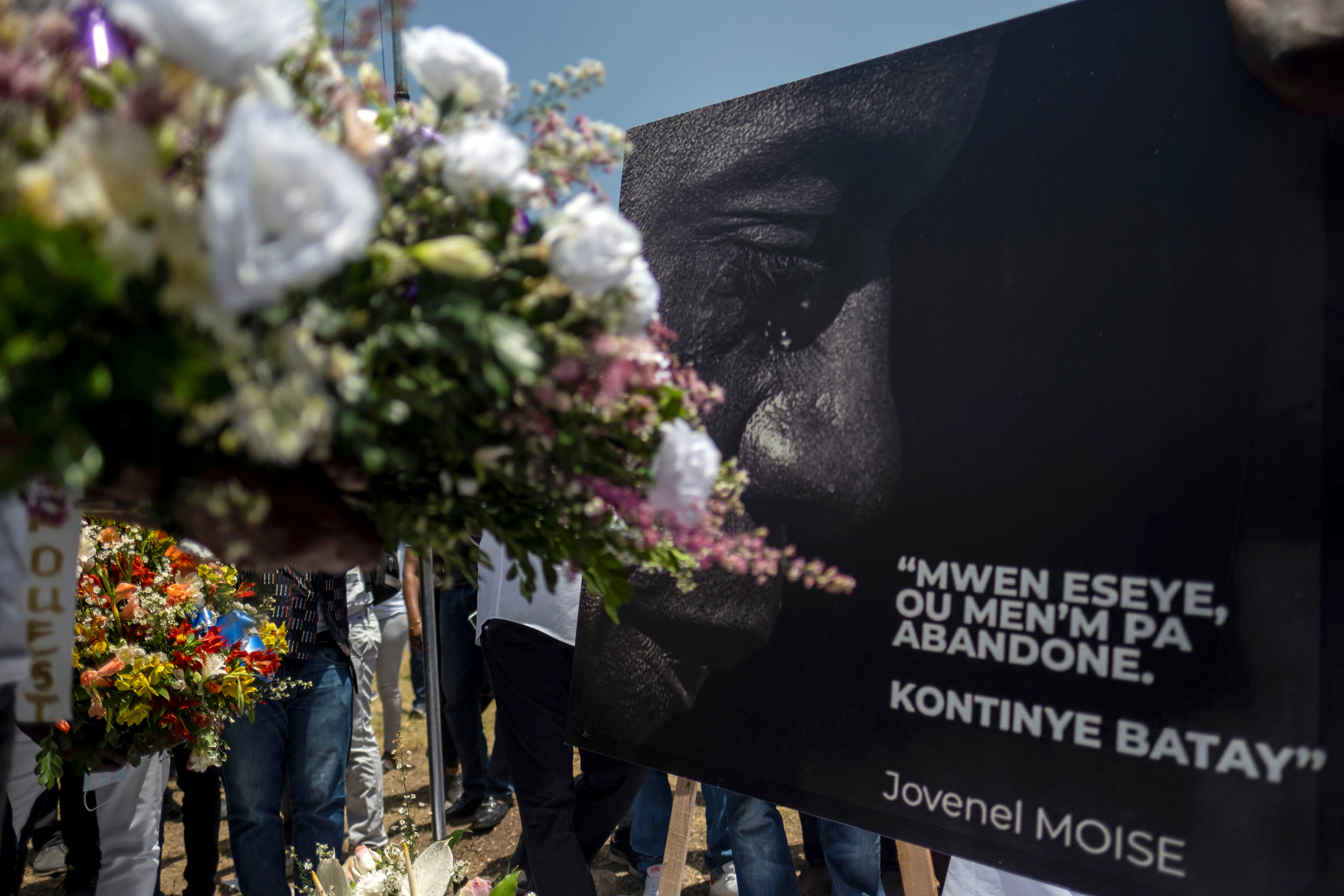 People place a portrait of late Haitian President Jovenel Moise with a quote from him that reads in creole